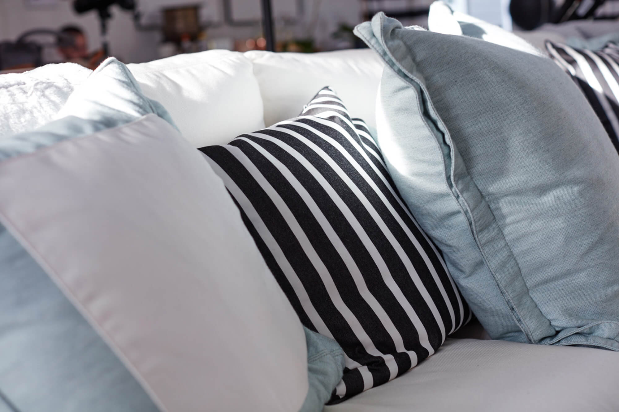 A white sofa gets a pop of color from teal pillows and black and white striped throw pillows