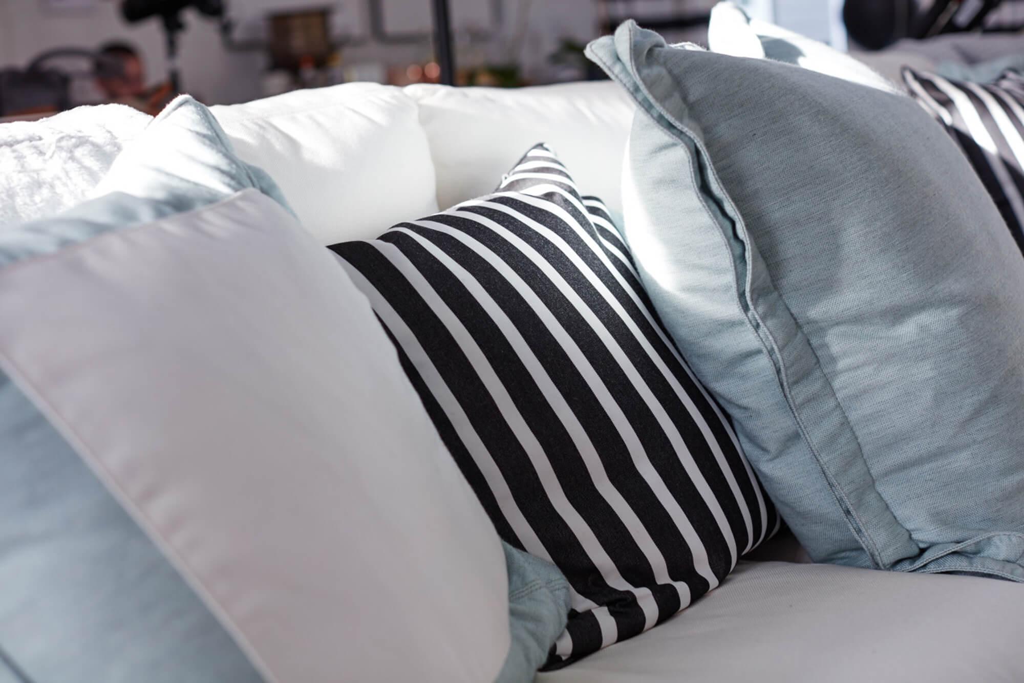 โซฟาสีขาวทำให้สีสดใสด้วยหมอนสีน้ำเงินเขียวและหมอนอิงสีขาวและดำลายทาง