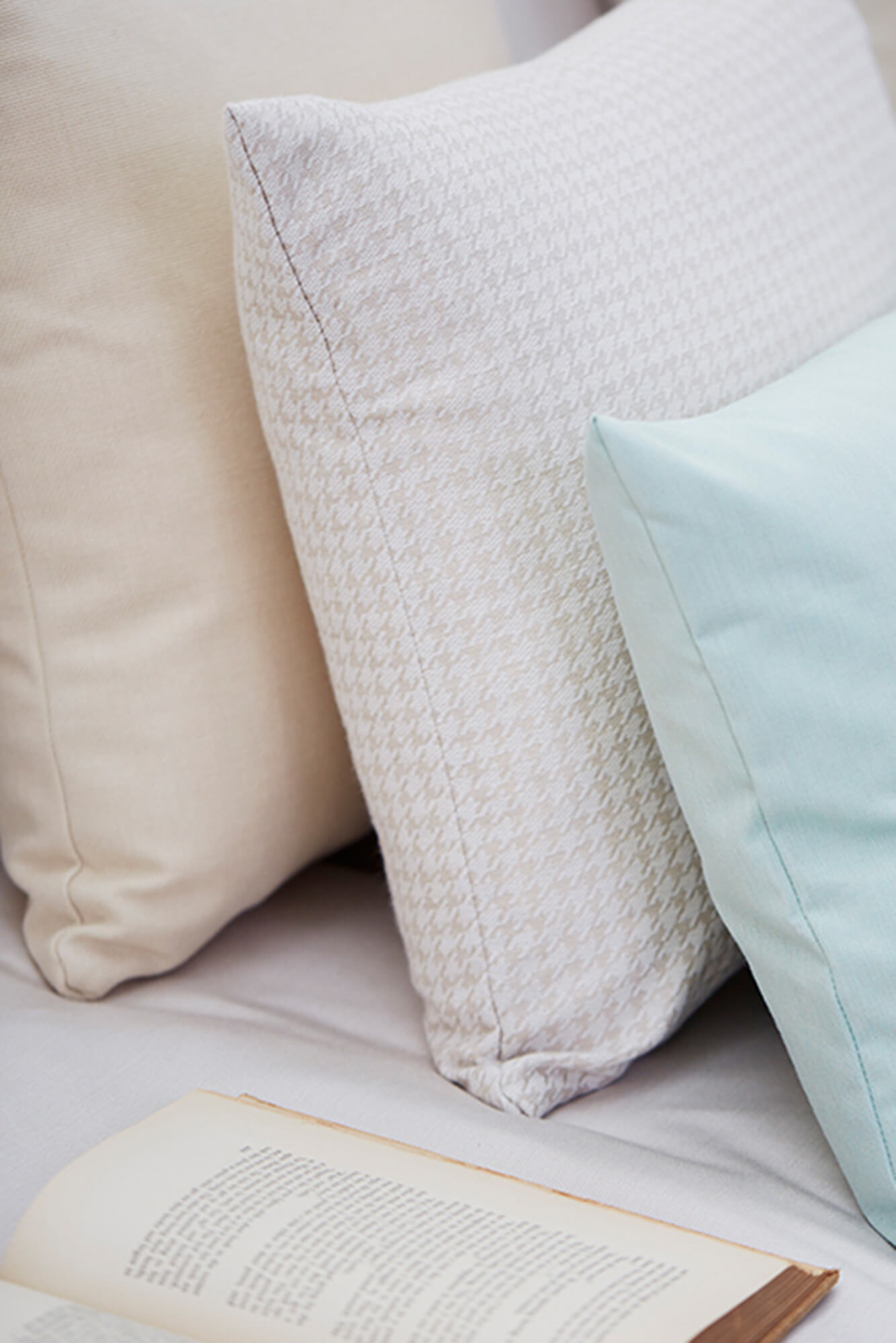 Neutral and teal pillows made using Sunbrella fabrics sit on a white sofa