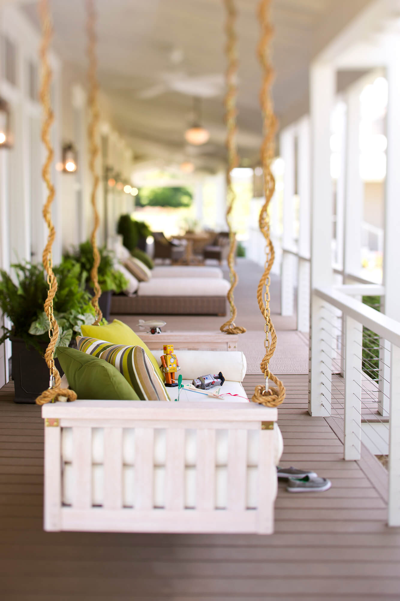 A porch swing is accented with green hued throw pillows