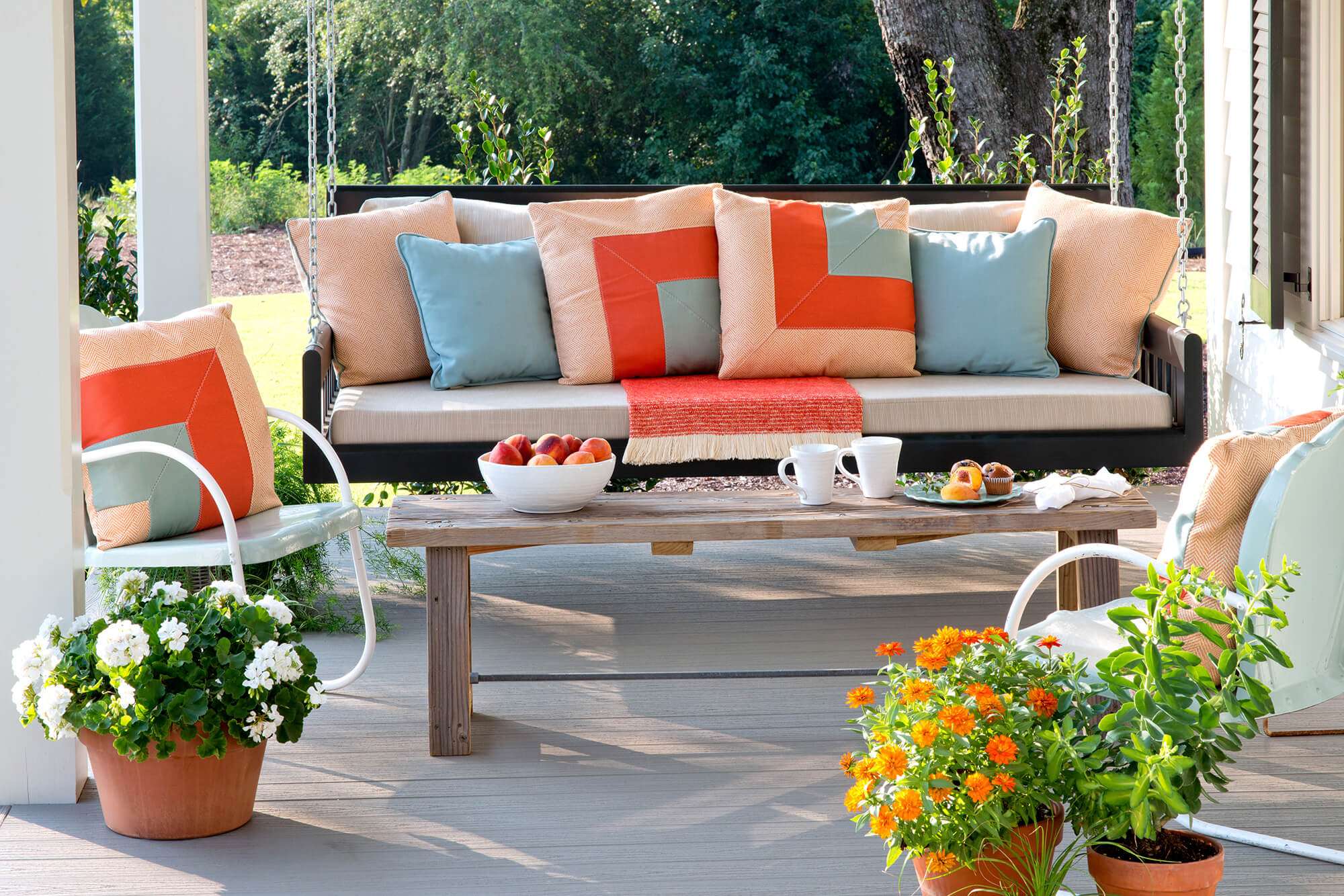 An outdoor porch swing lined with teal and peach colored decorative throw pillows