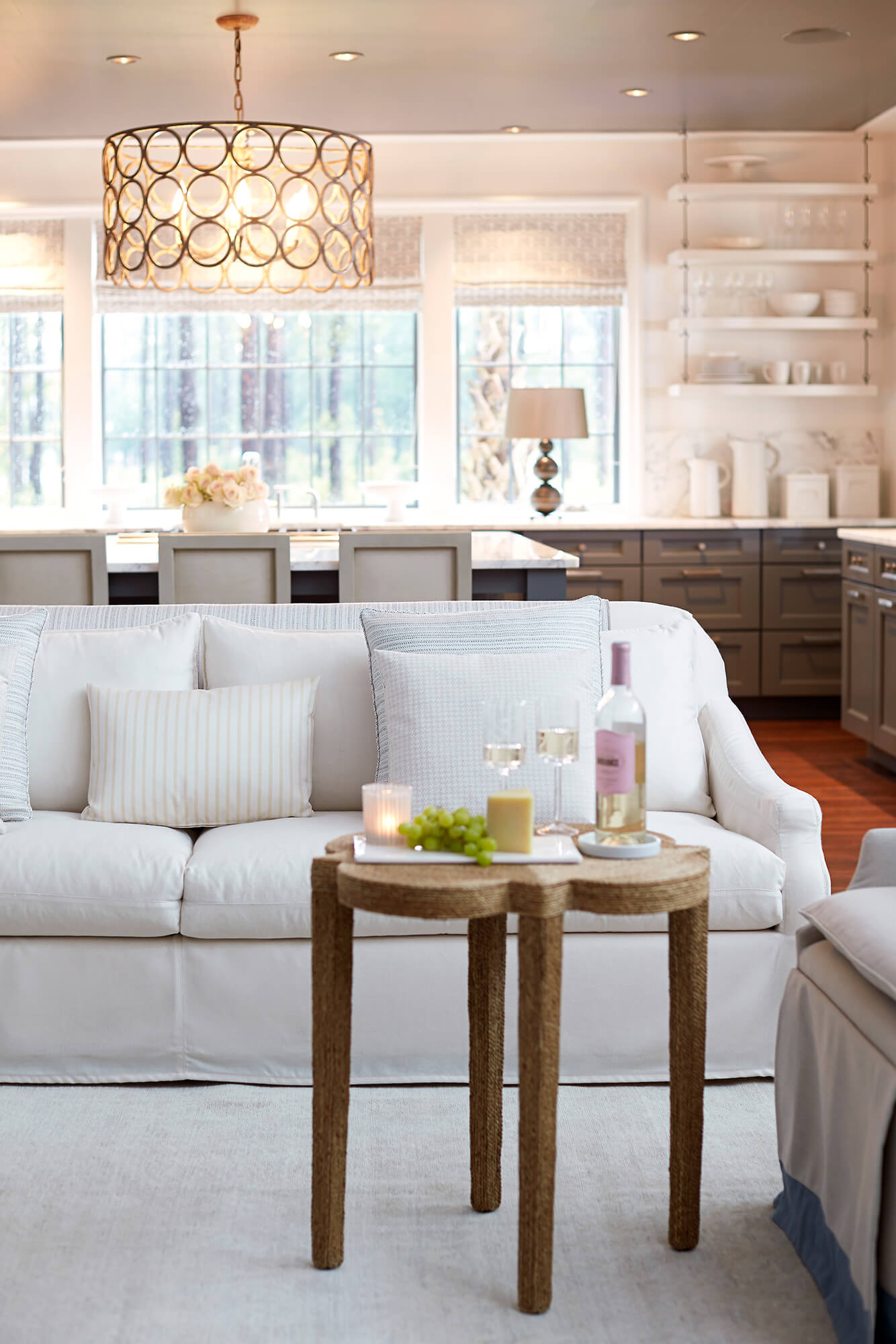 A white sofa upholstered in Sunbrella fabrics is accented with throw pillows of textured neutral hues