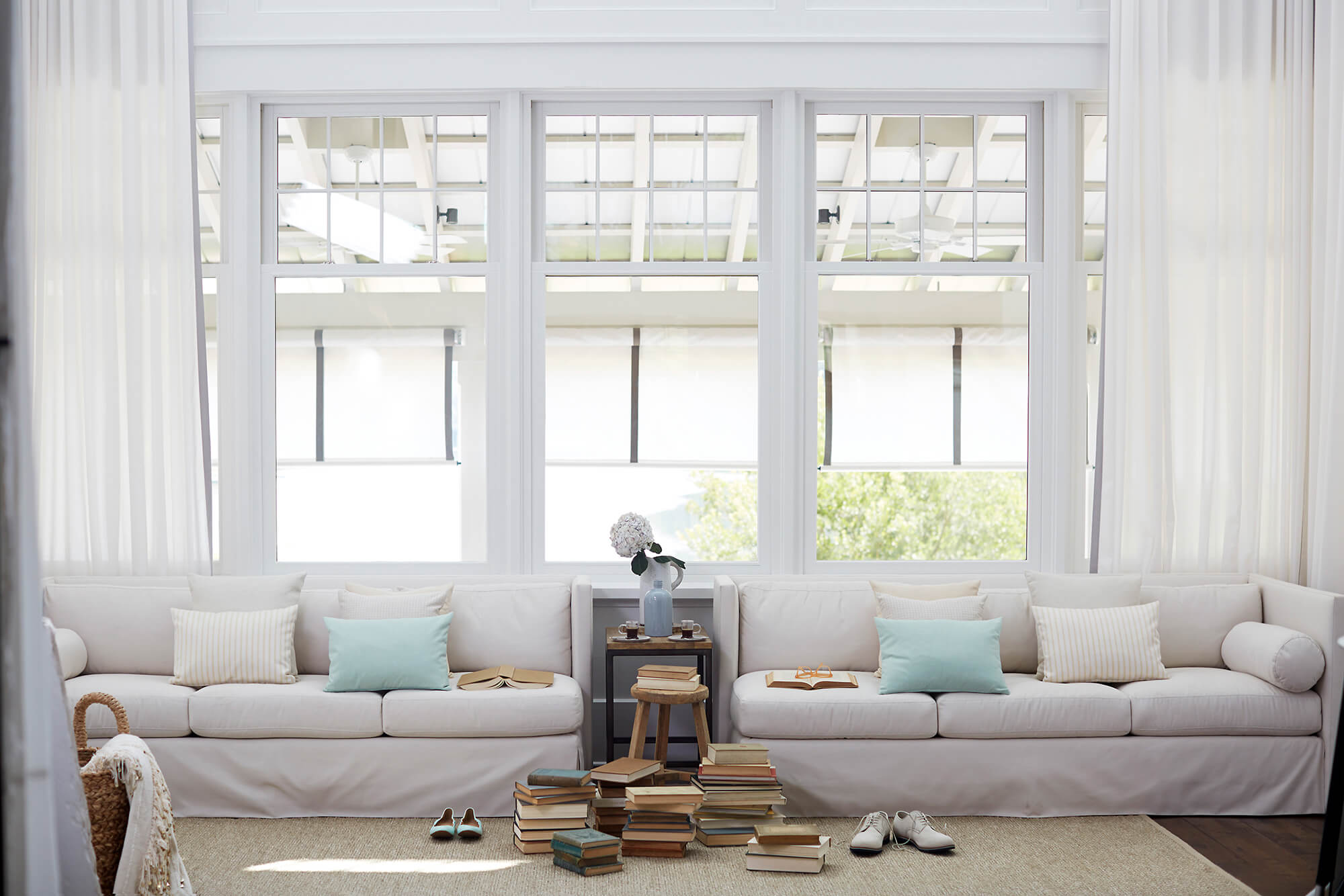 A white sofa upholstered in Sunbrella fabrics is decorated with neutral textured pillows and teal pillows