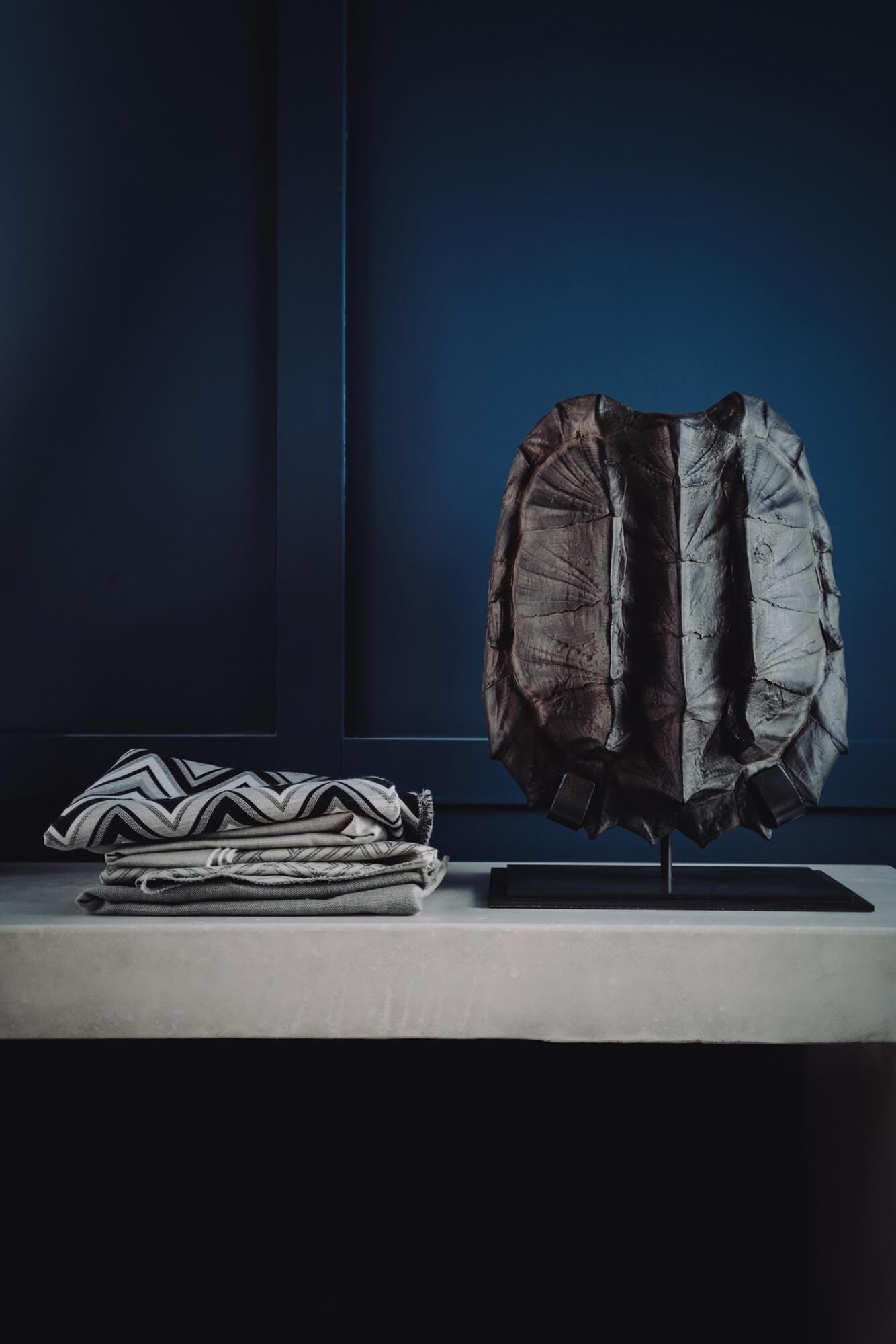 กองผ้าในโทนสีขาวและดำกองอยู่ข้างชิ้นงานศิลปะ