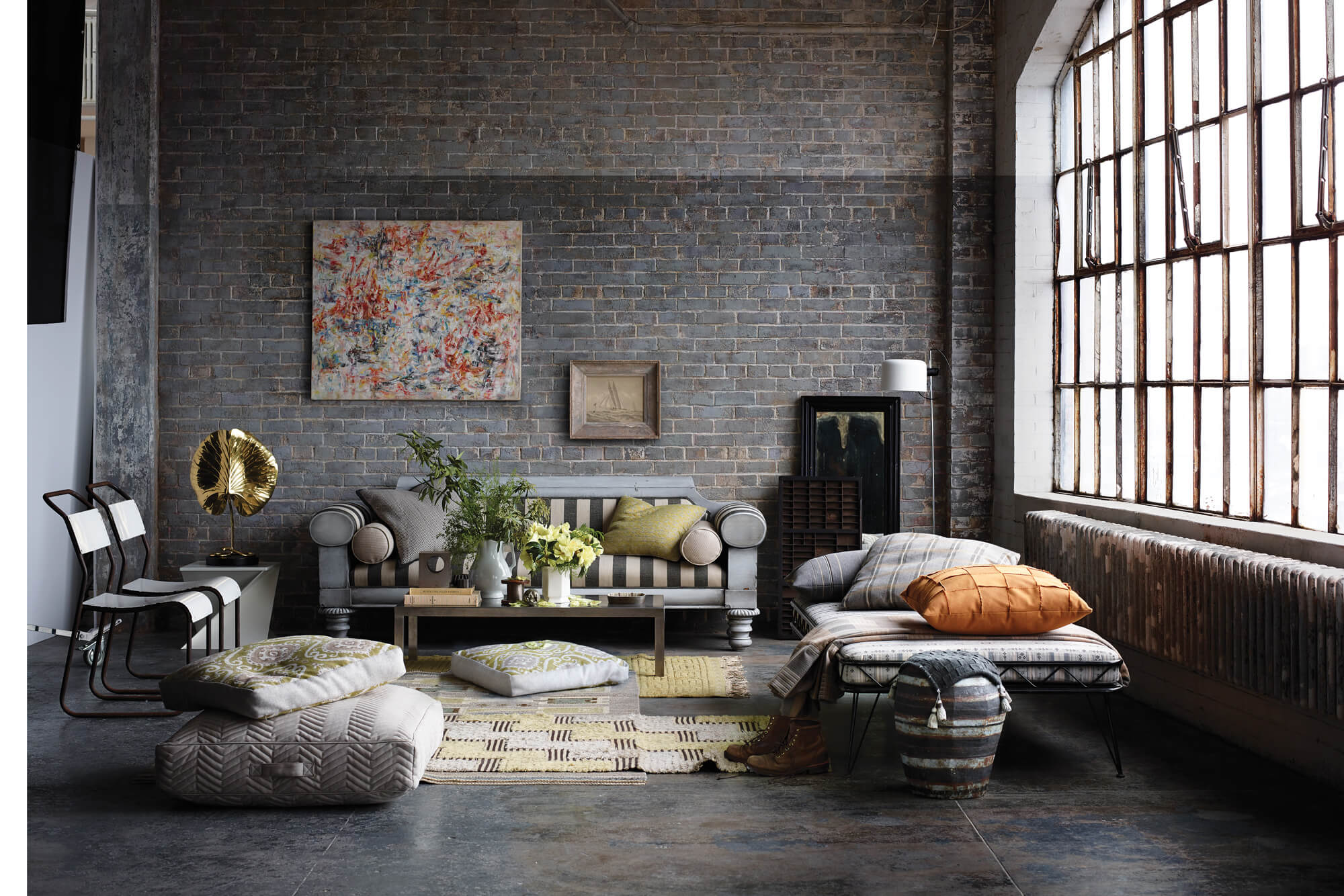 Un soggiorno ha al suo centro un divano a strisce bianche e nere con diversi accessori intorno alla stanza