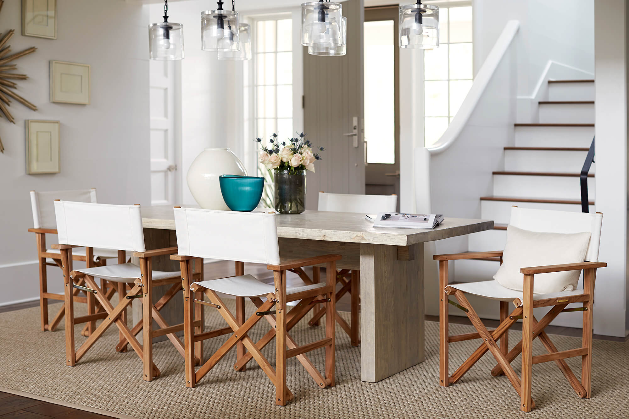 White directors chairs surround an indoor dining table