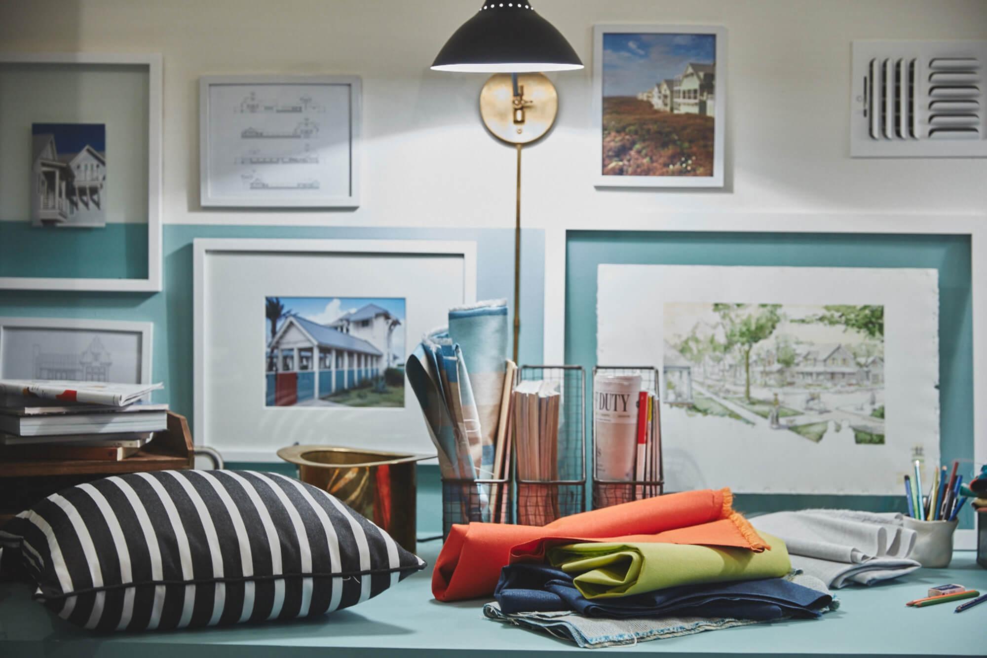 Lo spazio di lavoro di un designer con cuscini a strisce bianche e nere e tessuti accatastati