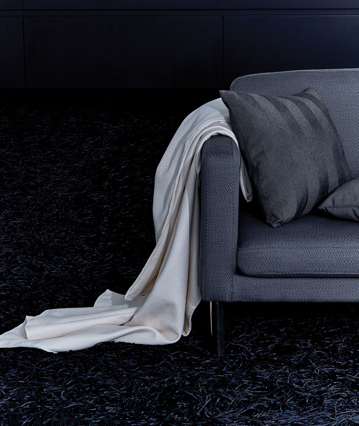 A grey sofa with a grey striped throw pillow and white throw blanket made using Sunbrella fabrics.