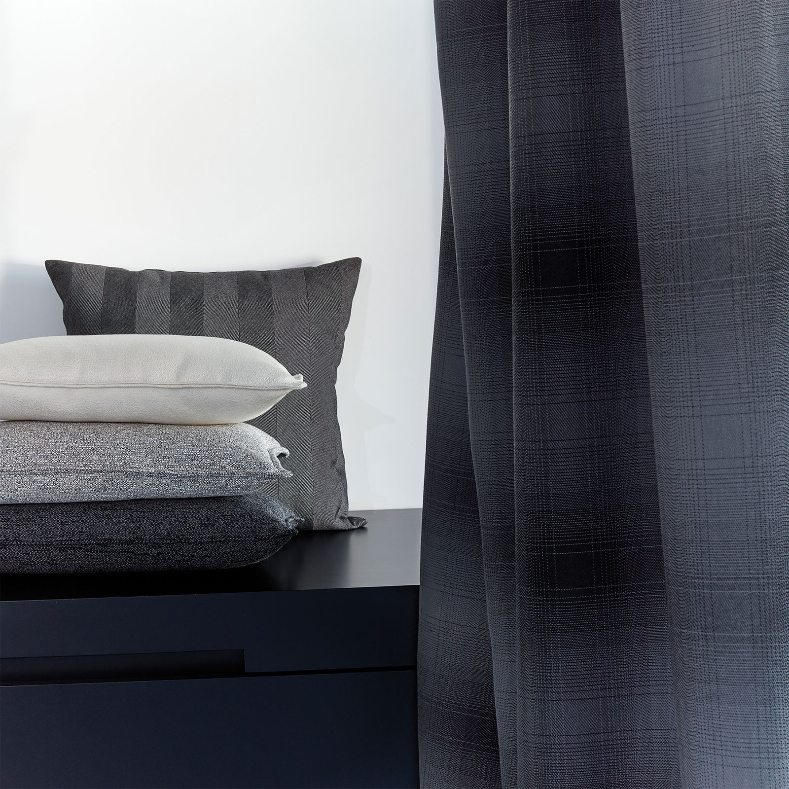 Neutral pillows of white, grey and black Sunbrella upholstery fabrics are stacked next to a grey drapery panel.