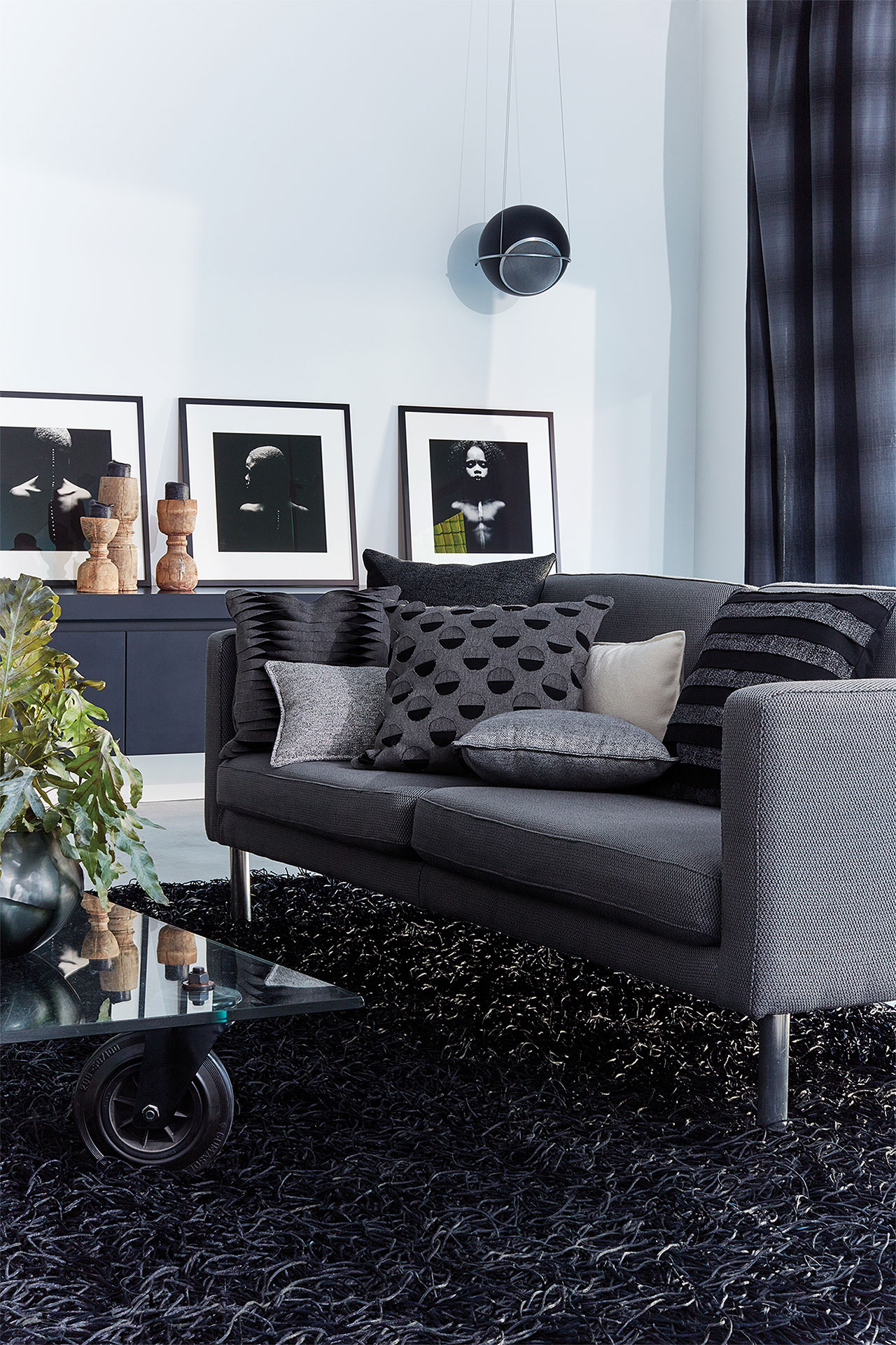 A living room is decorated in shades of black and white, with a grey sofa made with Sunbrella fabric in the center.
