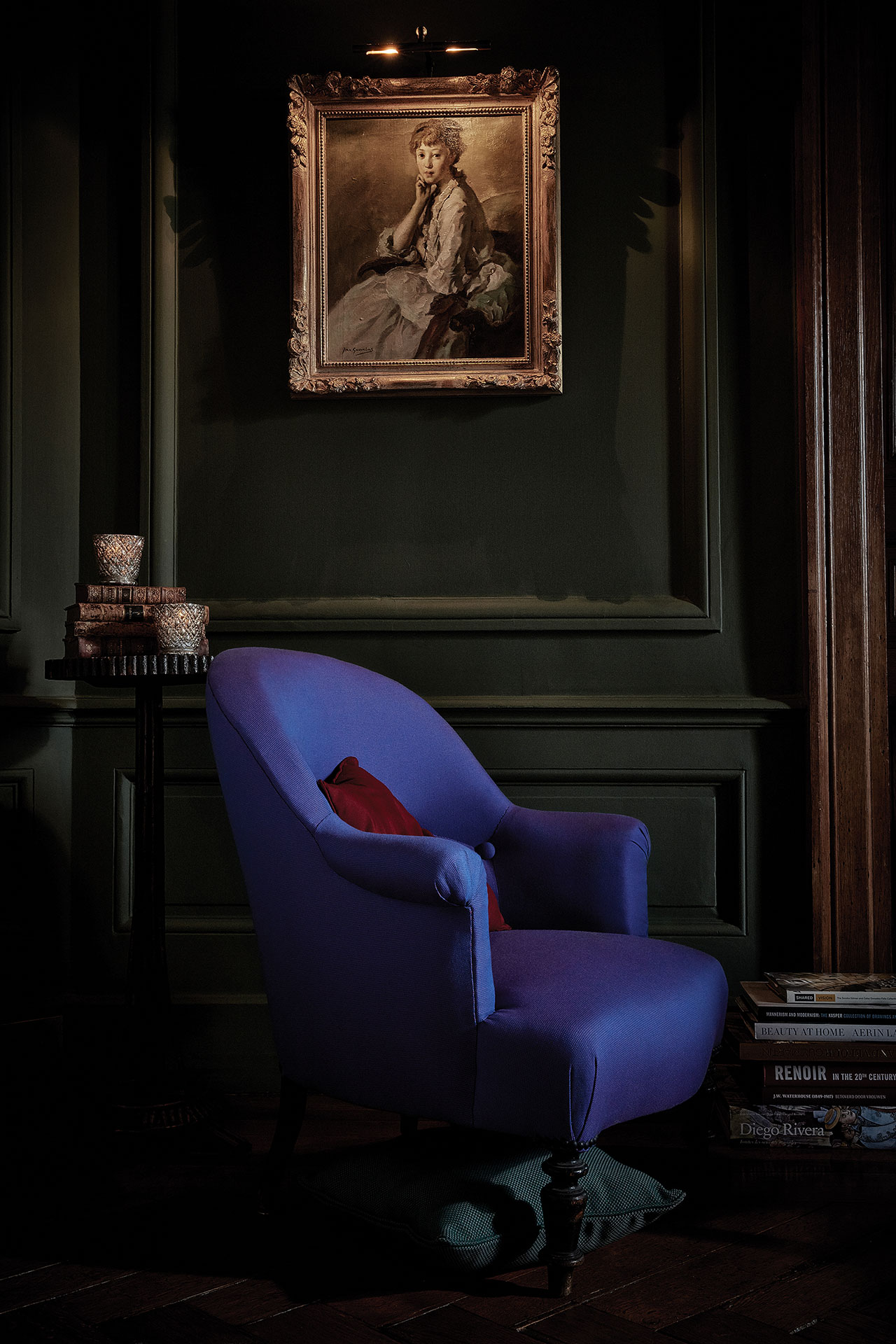 A chair upholstered in purple Sunbrella fabric pops in a dark room.