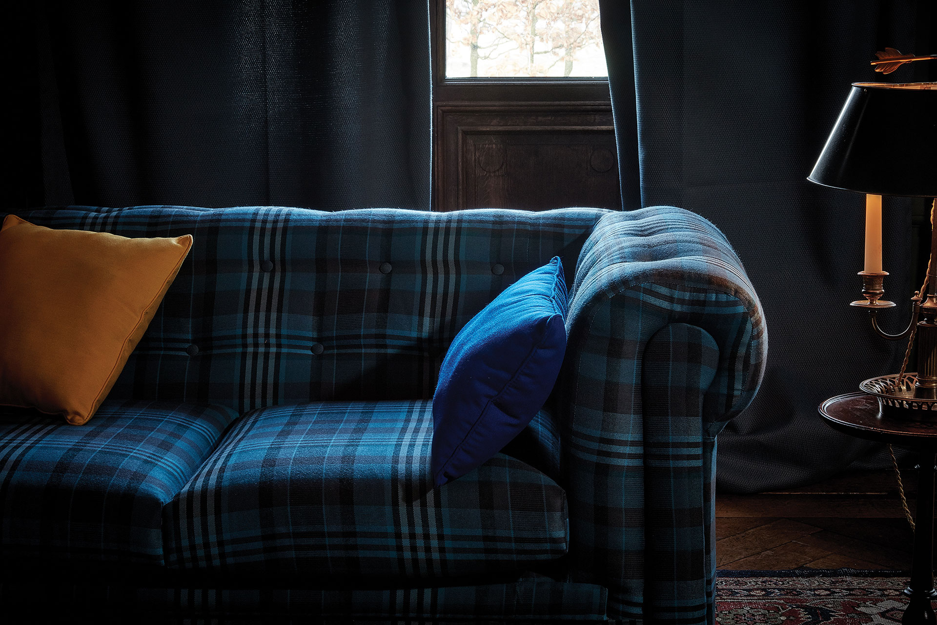 Close up of a sofa covered in a blue check Sunbrella upholstery fabric.