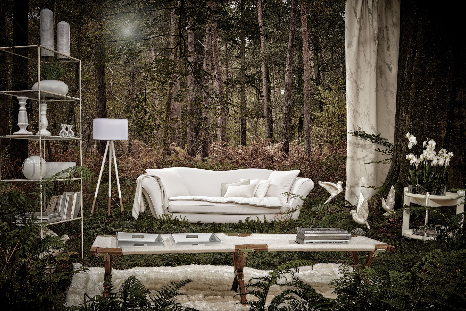 An indoor living room setting is placed outside in a forest, centered around a sofa covered with white Sunbrella fabric.