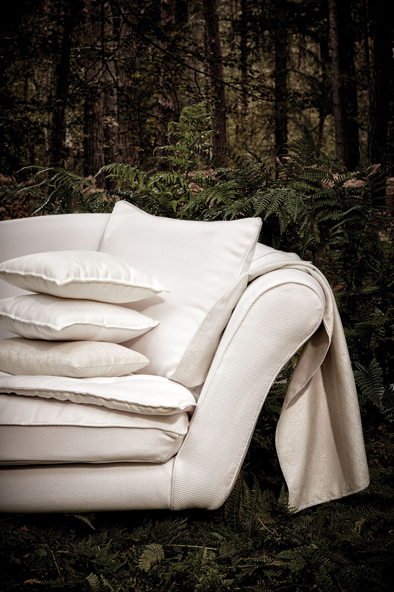 A close up of the arm of a white sofa covered in Sunbrella fabric.