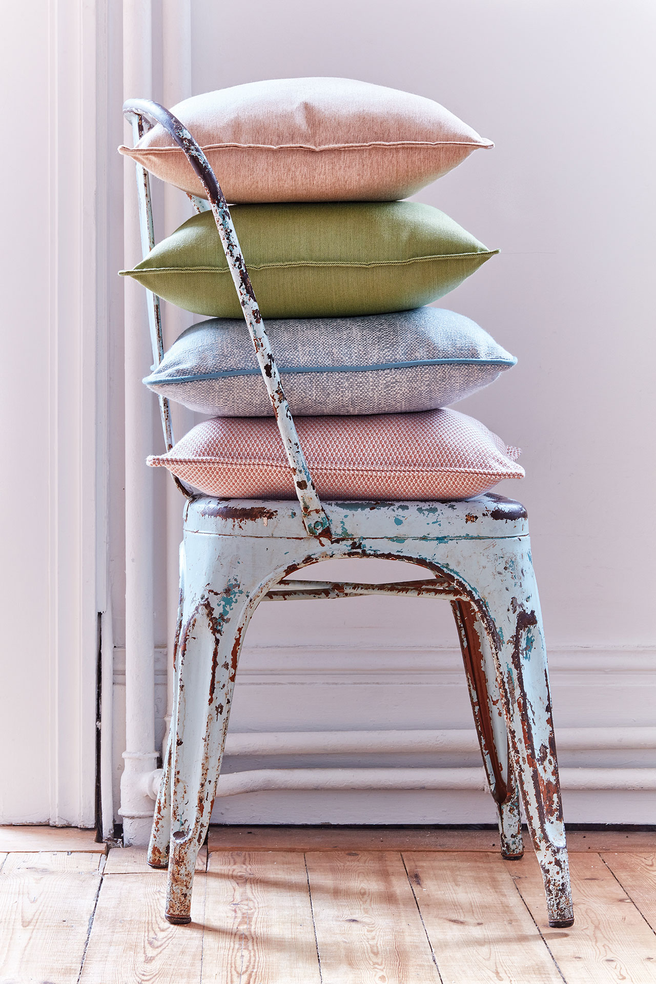 Pastel pillows are stacked on a distressed metal chair.