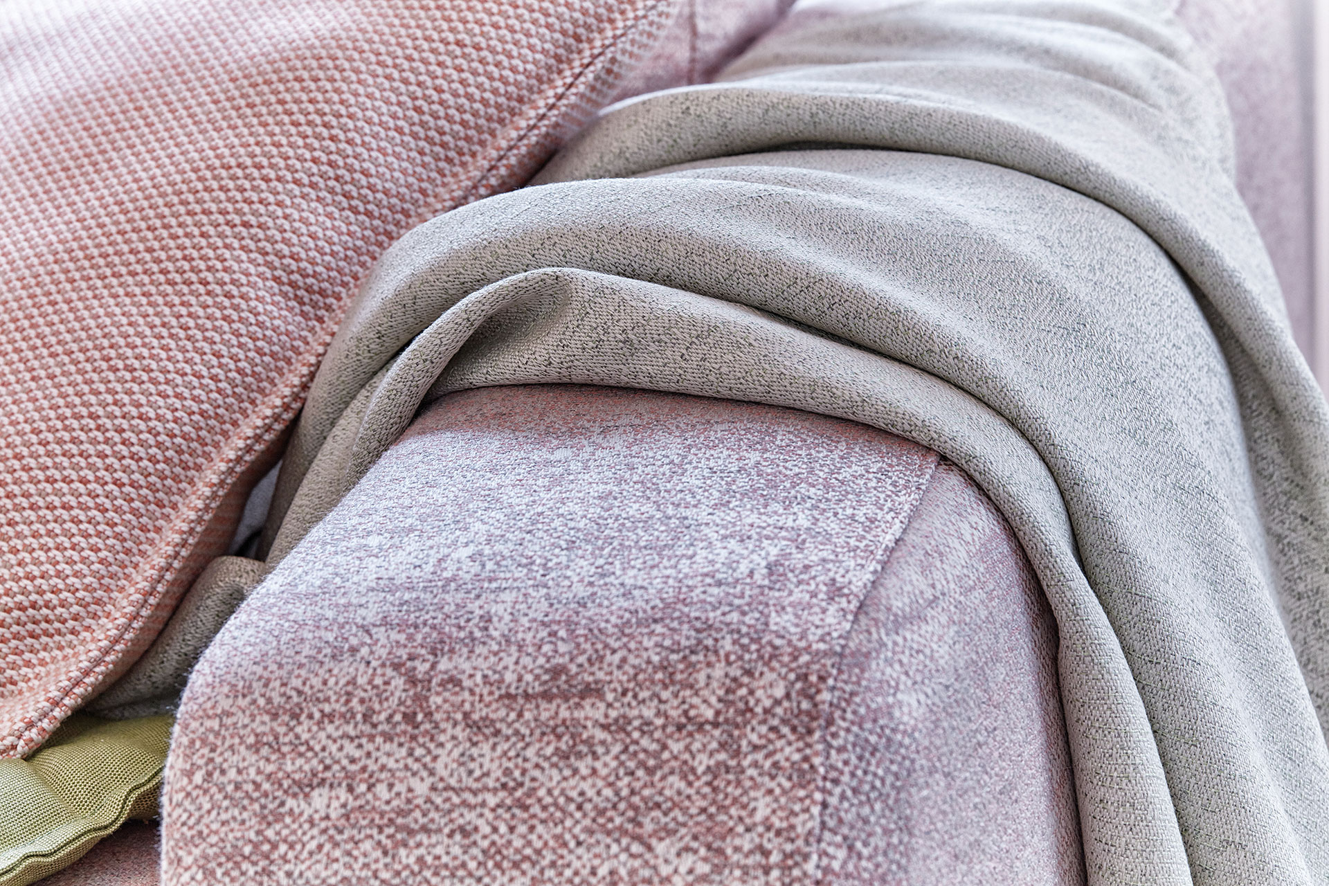 Close up of the arm of a pink sofa.