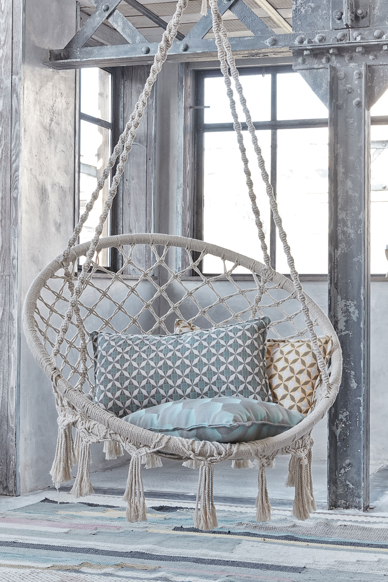 A swing chair with blue pillows.