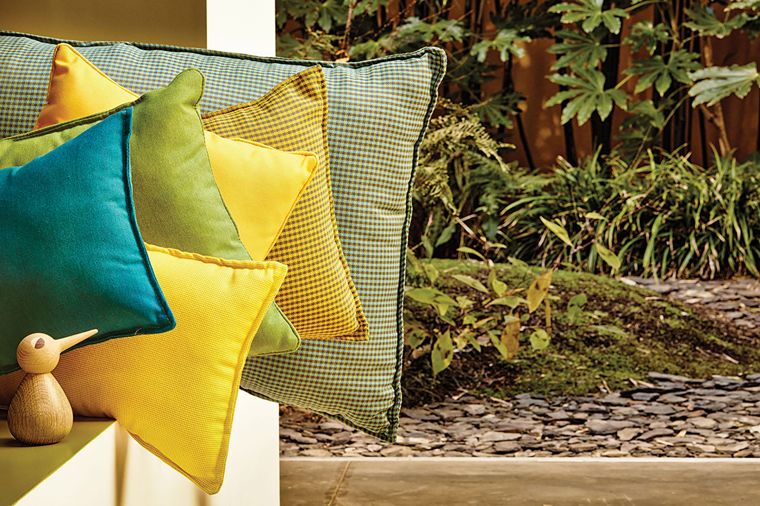 Blue, teal, and yellow pillows made using Sunbrella fabrics.
