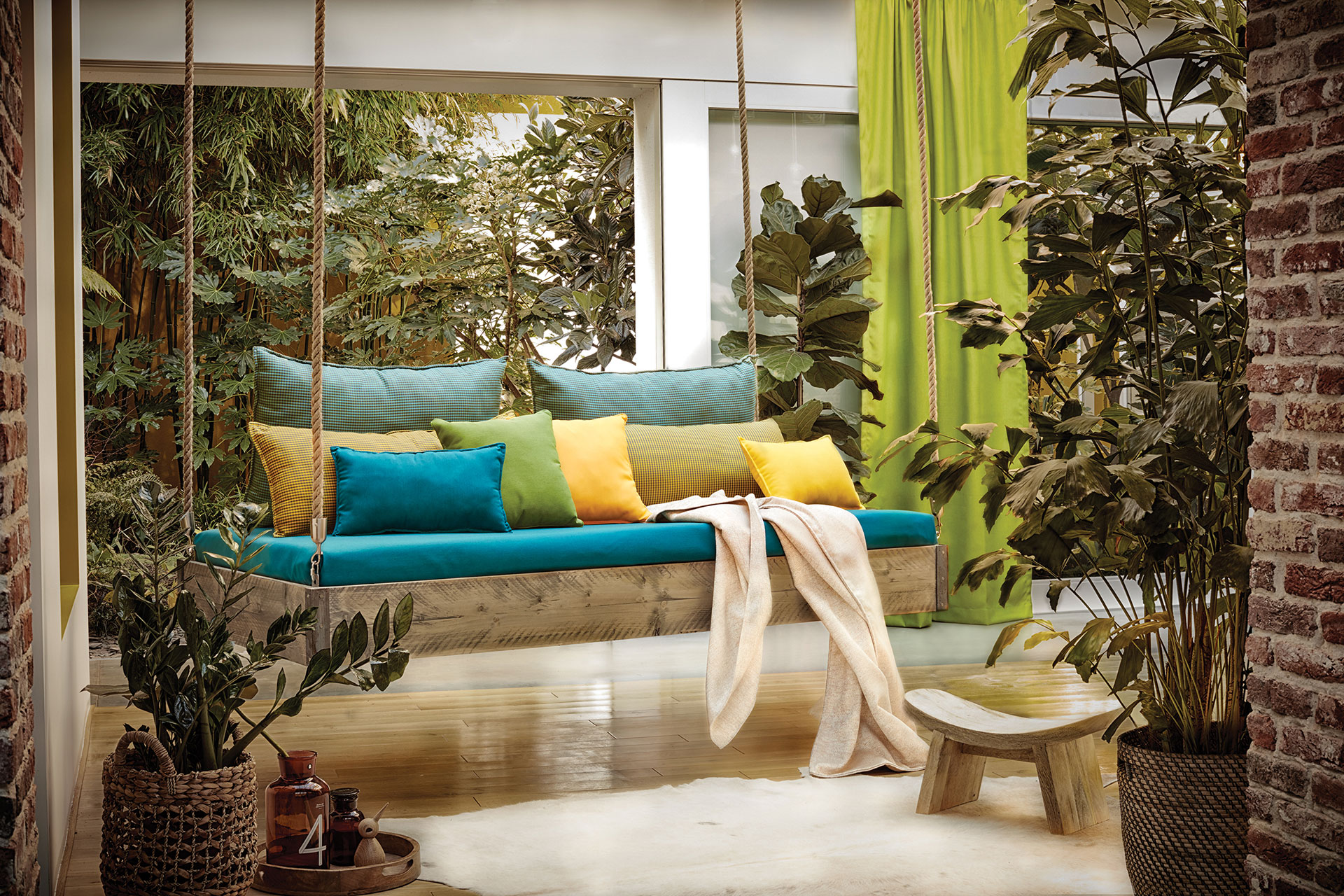 A swing with teal cushions in accented with bright pillows in yellow, green, and teal pillows with green drapery in the background.