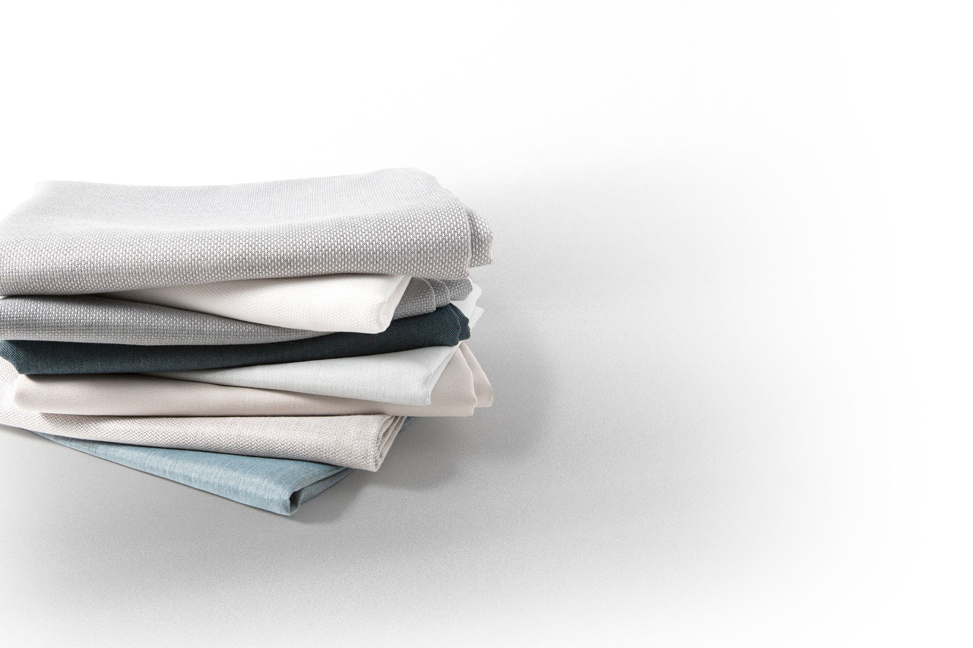 Closeup image of a folded stack of Sunbrella European Window Fabrics.