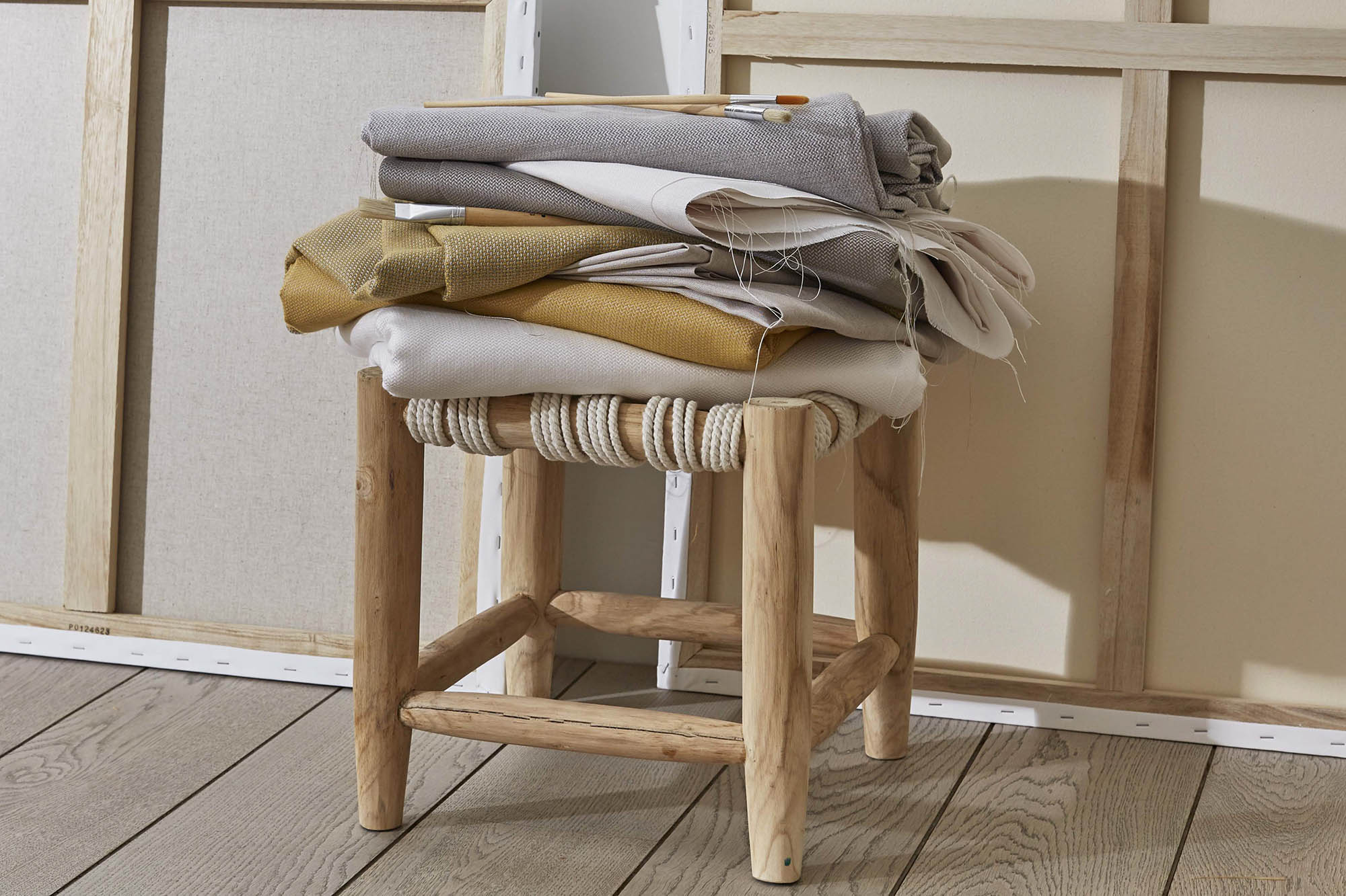 stack of folded sunbrella fabrics on stool