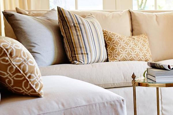 Sofa and chairs in neutral Sunbrella upholstery use pattern and texture to add interest