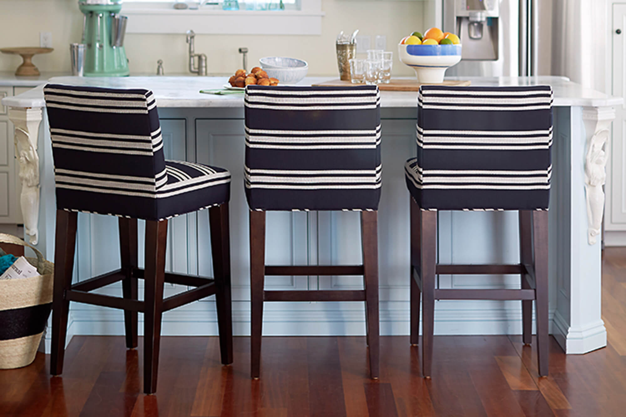 A beach house kitchen with a nautical touch with navy and white striped Sunbrella upholstered barstools