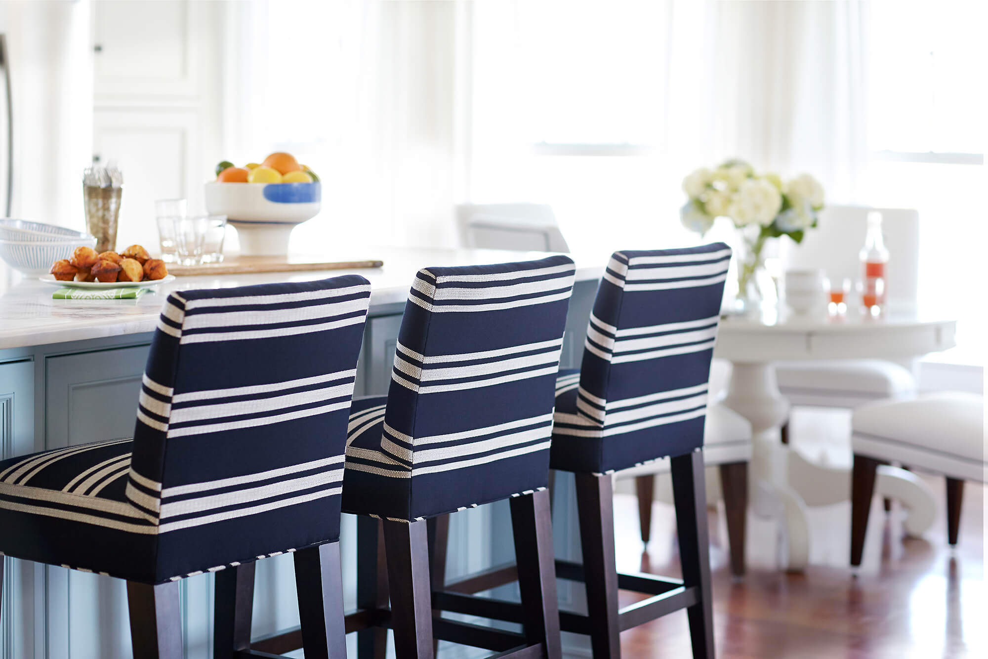 Navy and white striped upholstered barstools are a classic statement in this kitchen