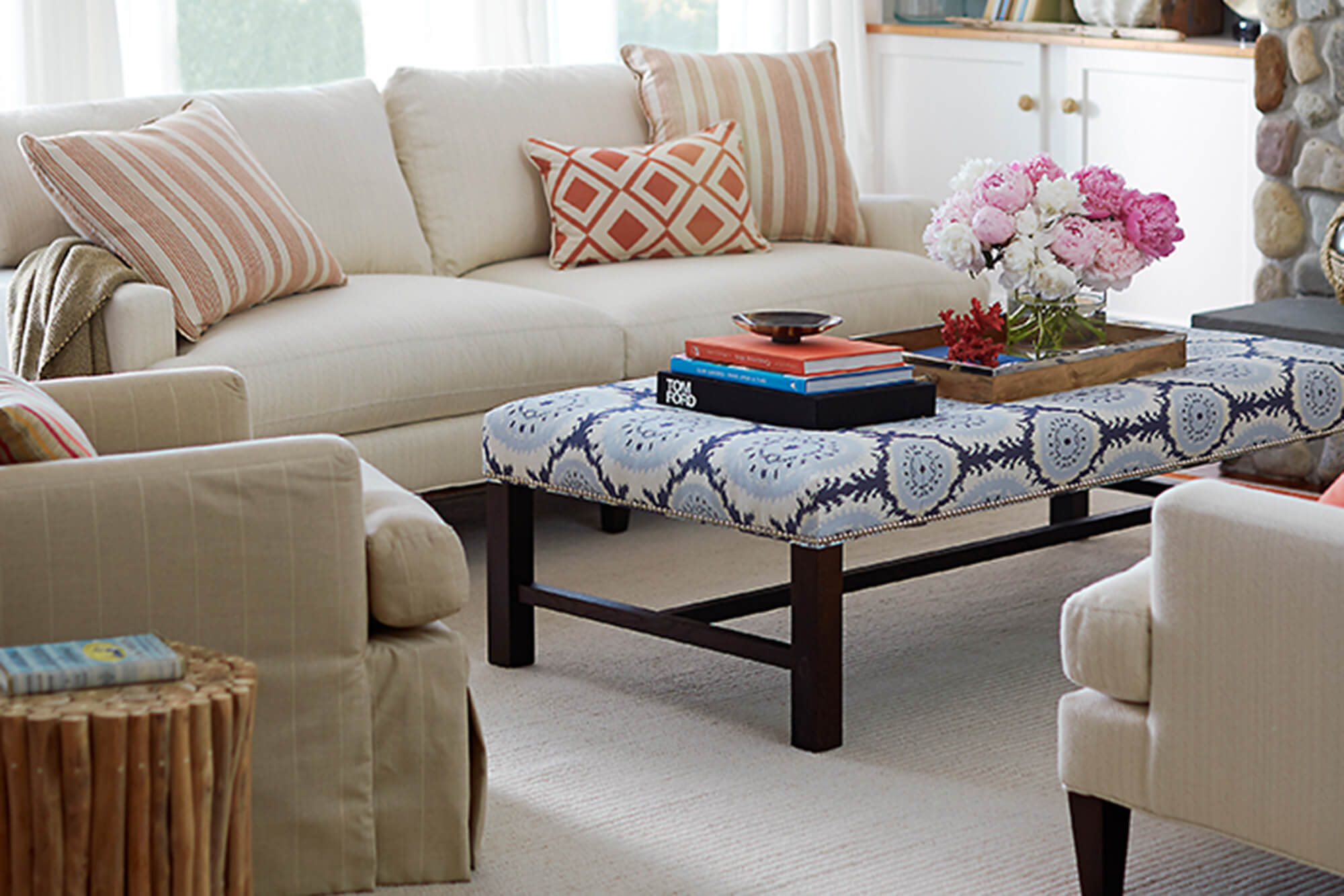 A blue jacquard patterned ottoman centers a living room and coordinates with the orange accents around the room