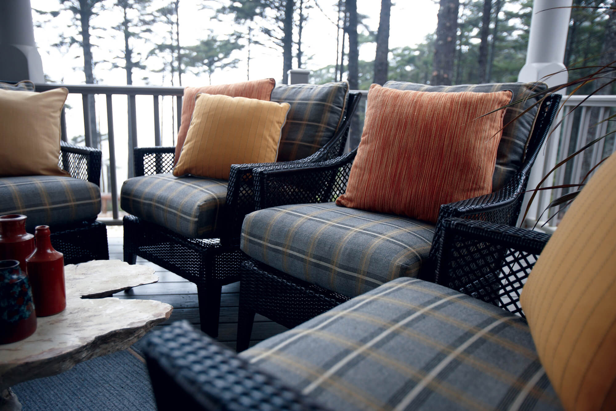 An outdoor patio looks ready for fall with grey plaid upholstery in Sunbrella Holmes Flannel