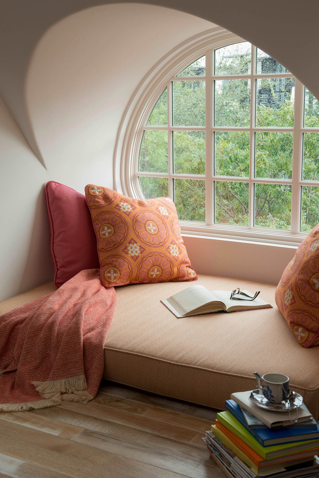 A cozy window seat is created with a plush floor cushion and oversized pillows in shades of pink and orange
