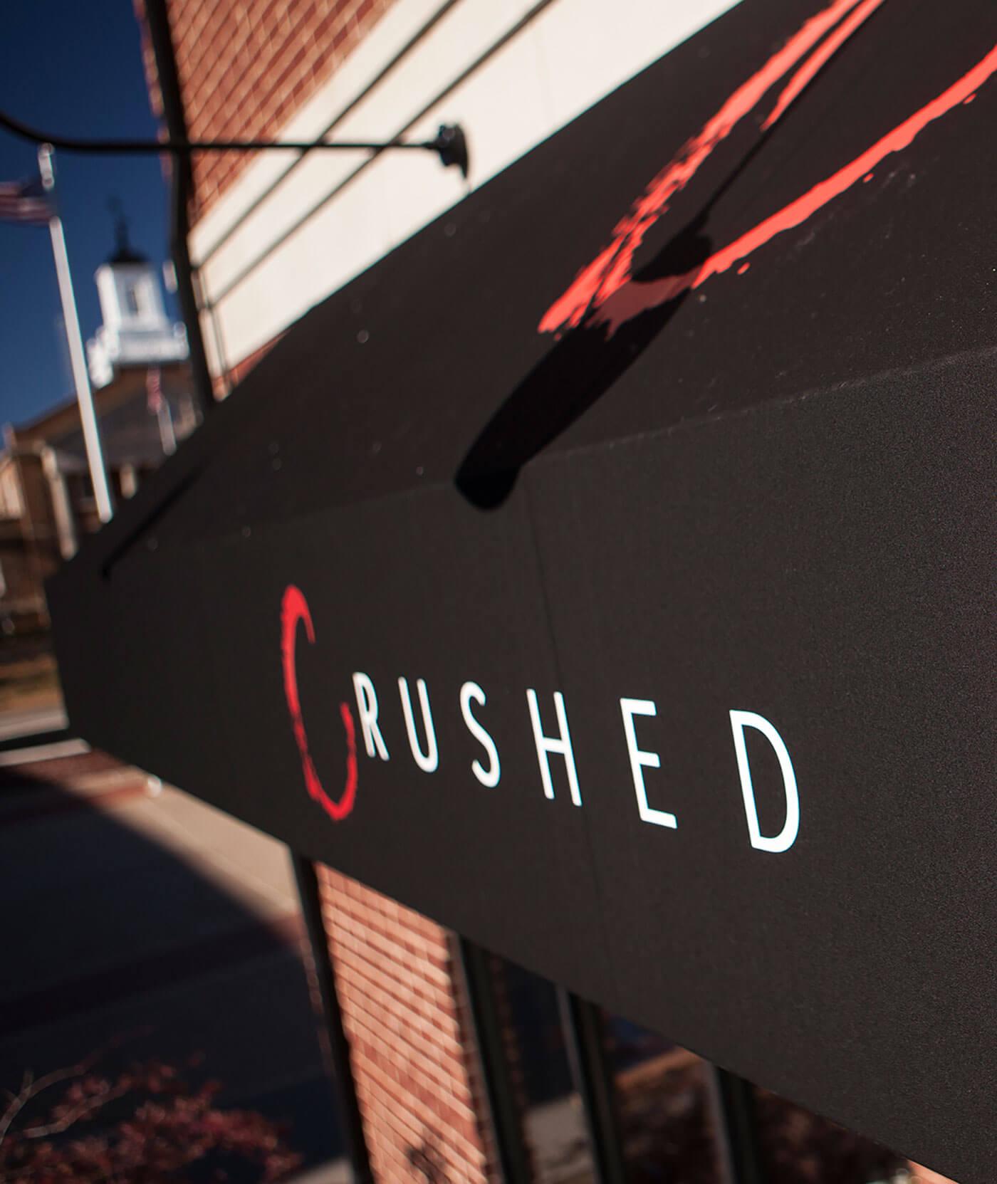 Toldo de estrutura fixa sobre um restaurante, com tecido preto e logotipos em vermelho, aplicadas pelo Sunbrella Graphics System