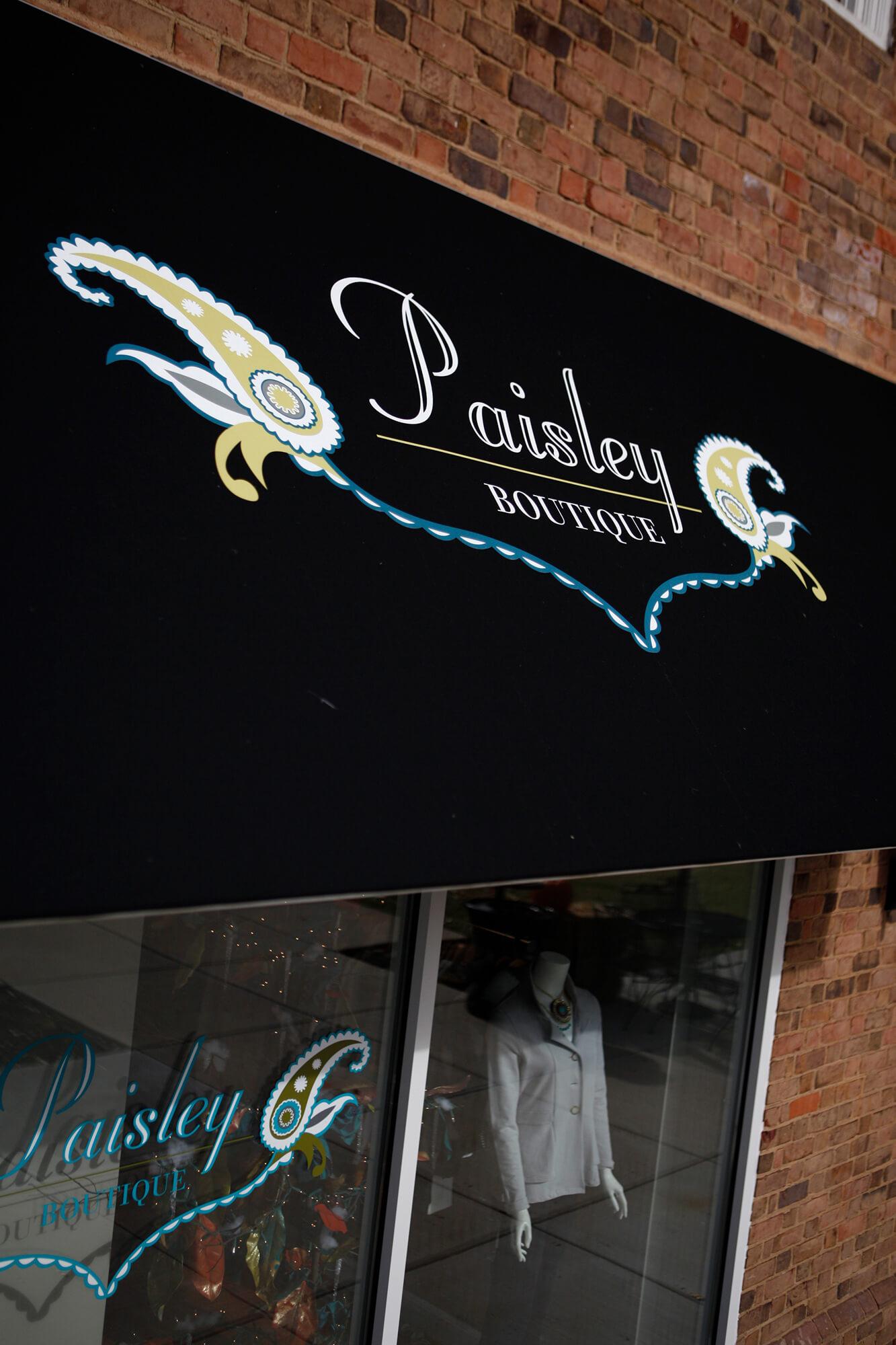 Cửa hàng boutique quảng cáo bằng mái che màu đen và biển hiệu ở mặt trước cửa hàng