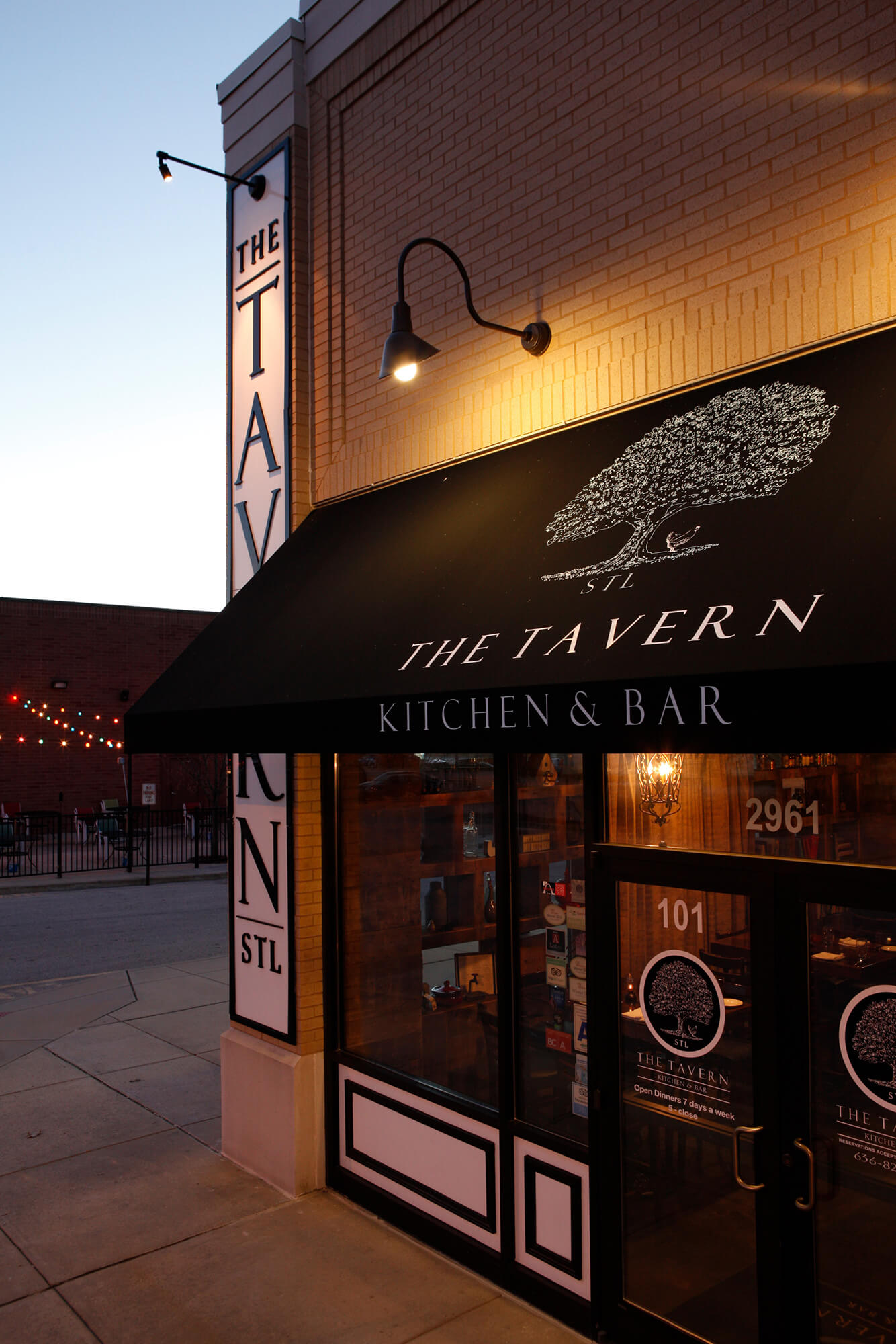 A tavern welcomes customers with a black awning