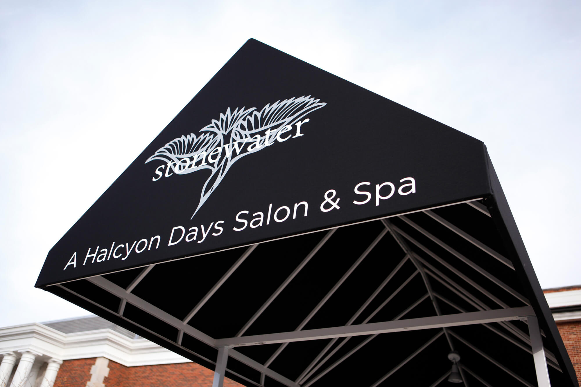 Un spa ofrece una entrada cubierta por un toldo con marco fijo para sus clientes