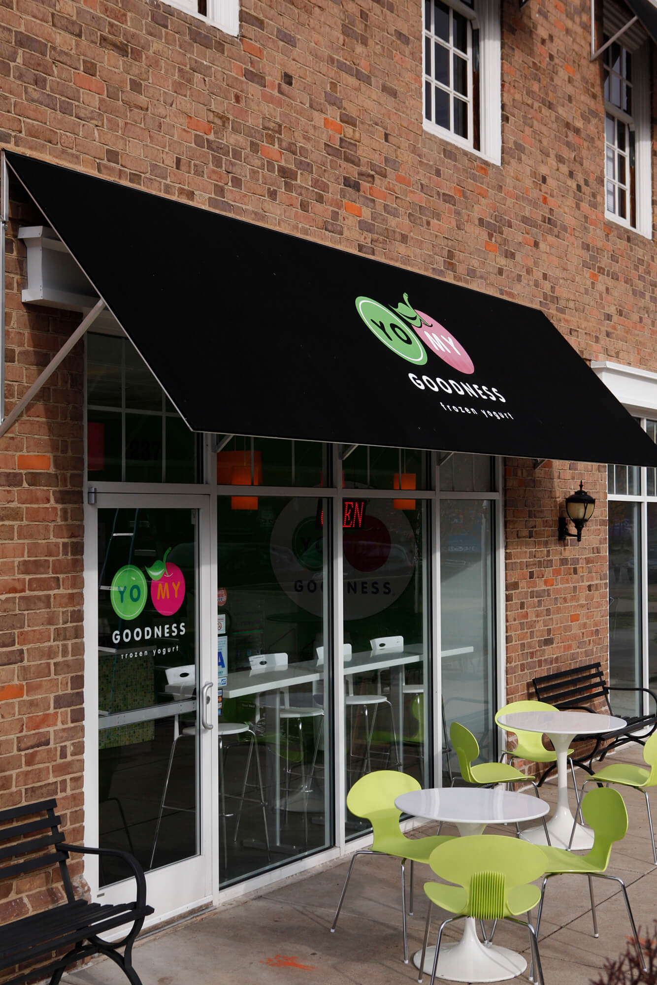 A yogurt shop welcomes customers with a black awning with graphics