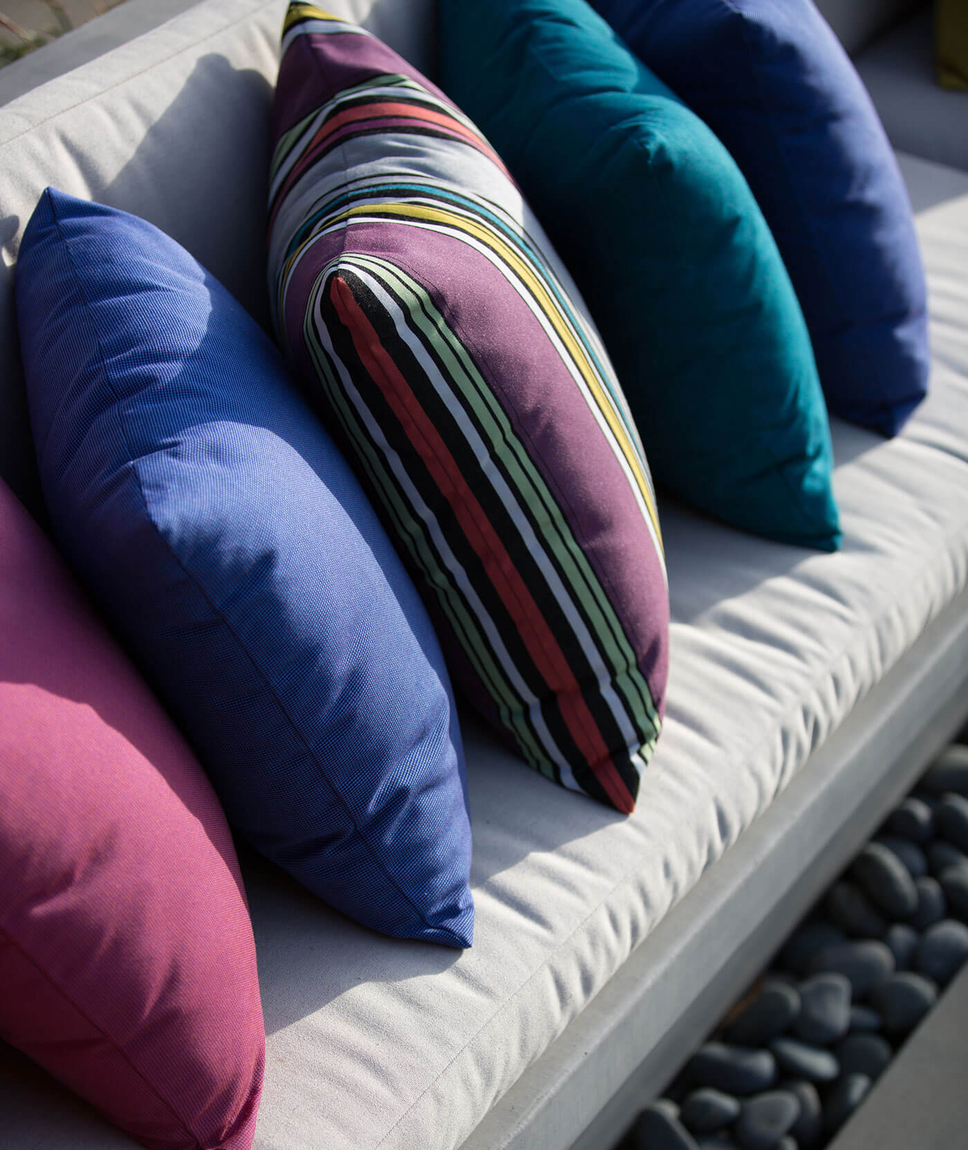 Close up of bright pillows made using Sunbrella fabrics on beige cushions