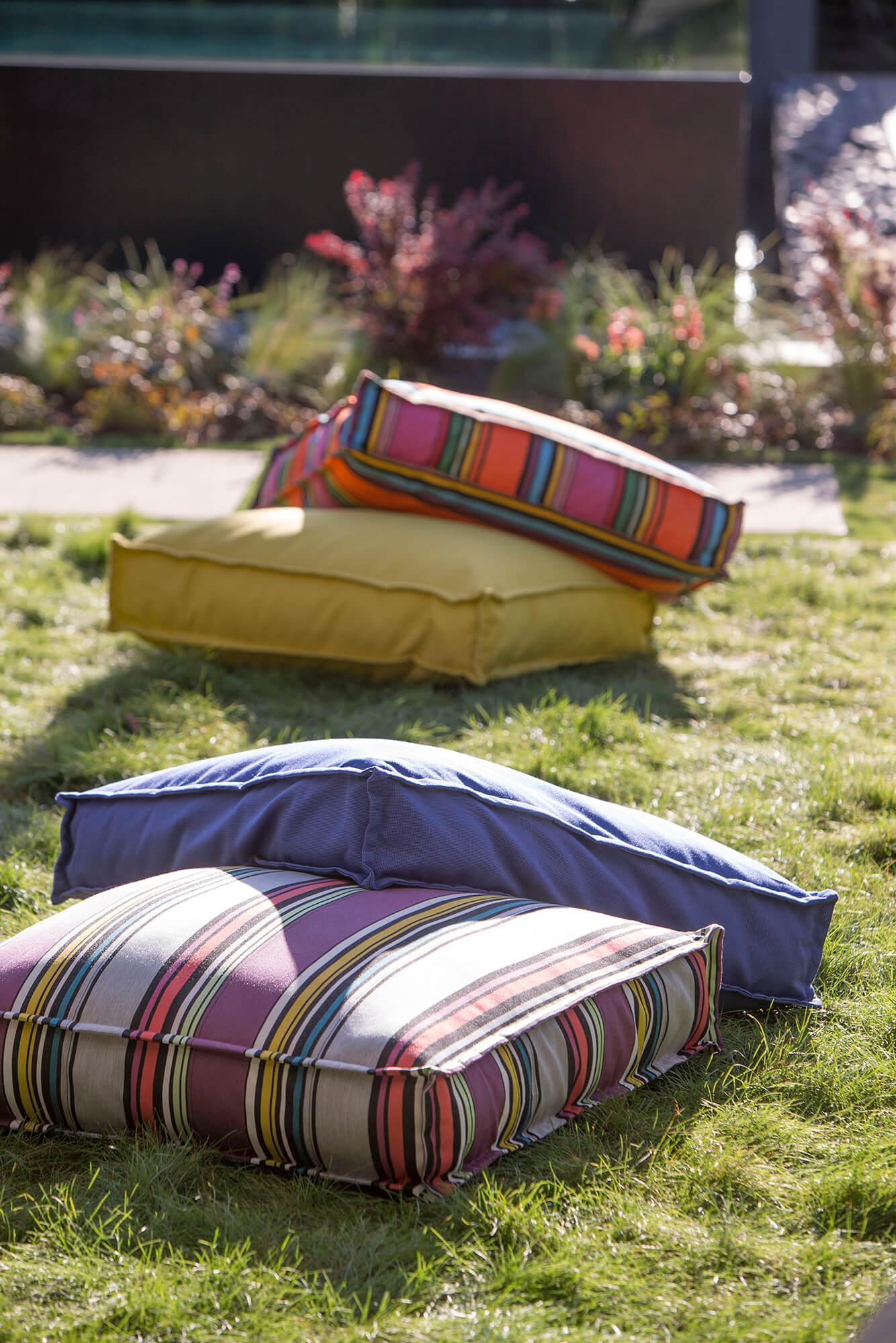กองหมอนรองพื้นสีสว่างหุ้มด้วยผ้า Sunbrella จากคอลเลกชัน Icon วางเรียงกันอยู่บนหญ้า
