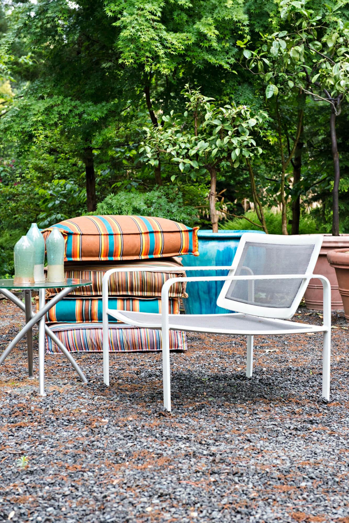 กองหมอนรองพื้นที่ด้านหลังเก้าอี้สนามในสวน
