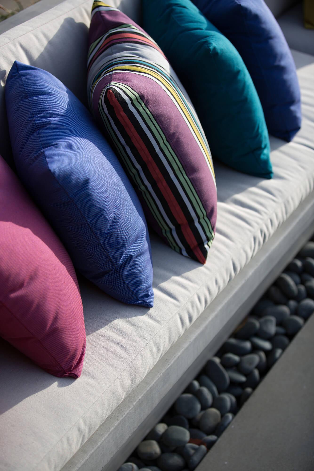 ภาพขยายของหมอนสีสว่างทำจากผ้า Sunbrella บนเบาะสีน้ำตาลอ่อน