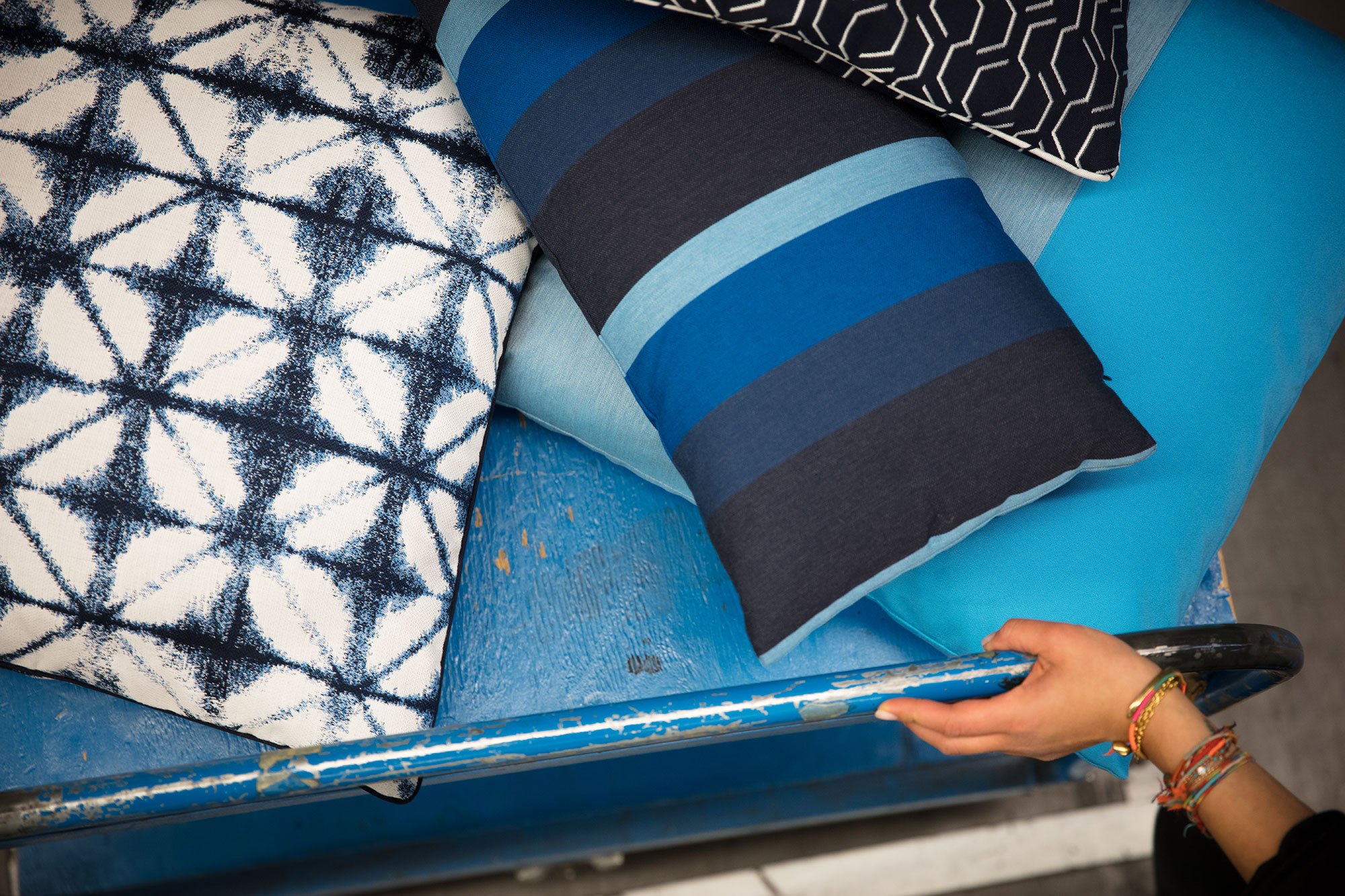 Blue pillows made with fabrics from the Sunbrella Makers upholstery fabric collection.