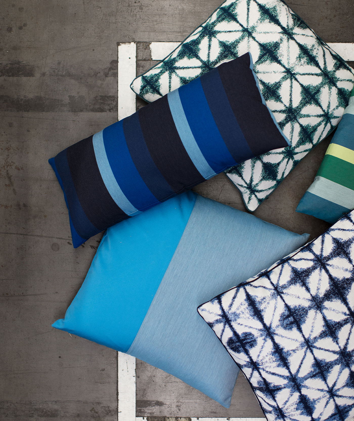 Pillows in blue and green hues are stacked, featuring the Sunbrella Makers fabric collection.