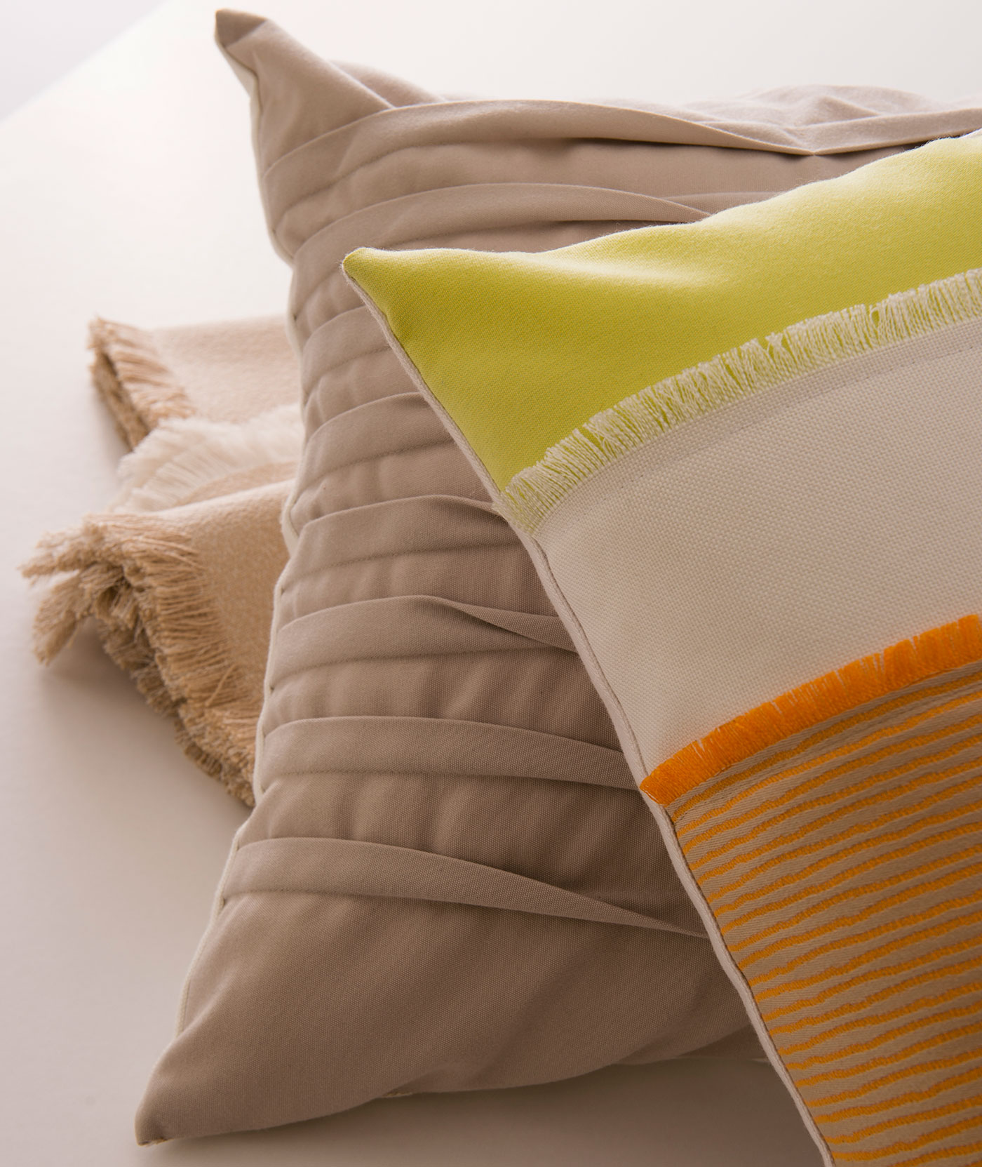 Close up of neutral pillows with pops of orange and citron.