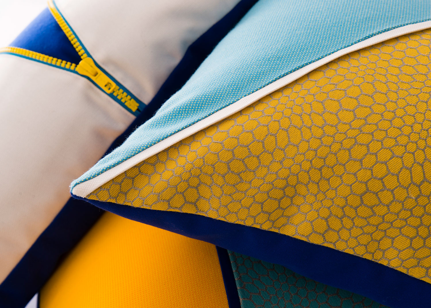 Close up of pillows made with bright blue and yellow Sunbrella fabrics.
