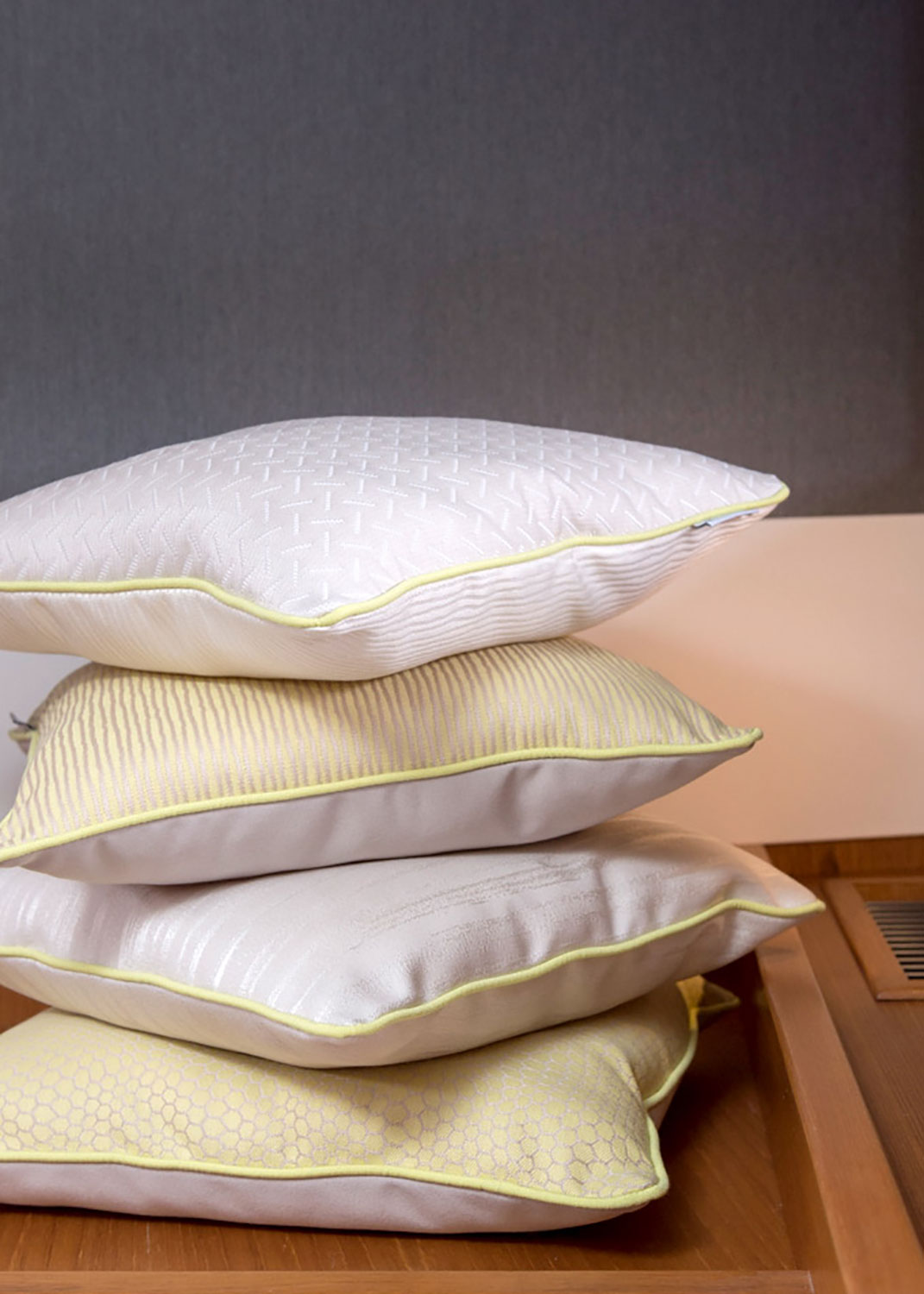 Stacked pillows made using beige and yellow Sunbrella fabrics.