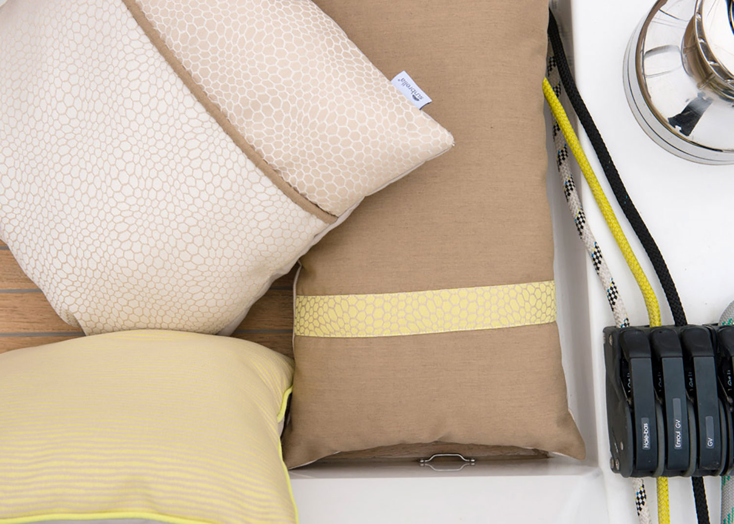 Beige and yellow pillows made using Sunbrella fabrics are arranged on a boat deck.