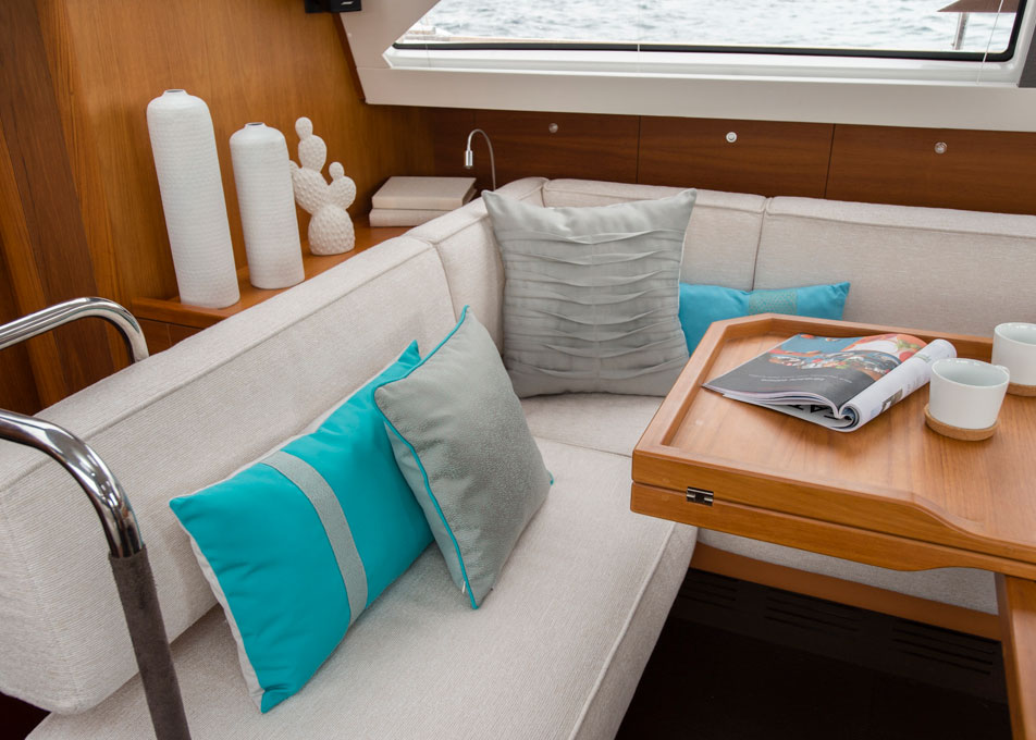 A boat cabin's dining area has a pop of color with teal pillows made using Sunbrella fabrics.