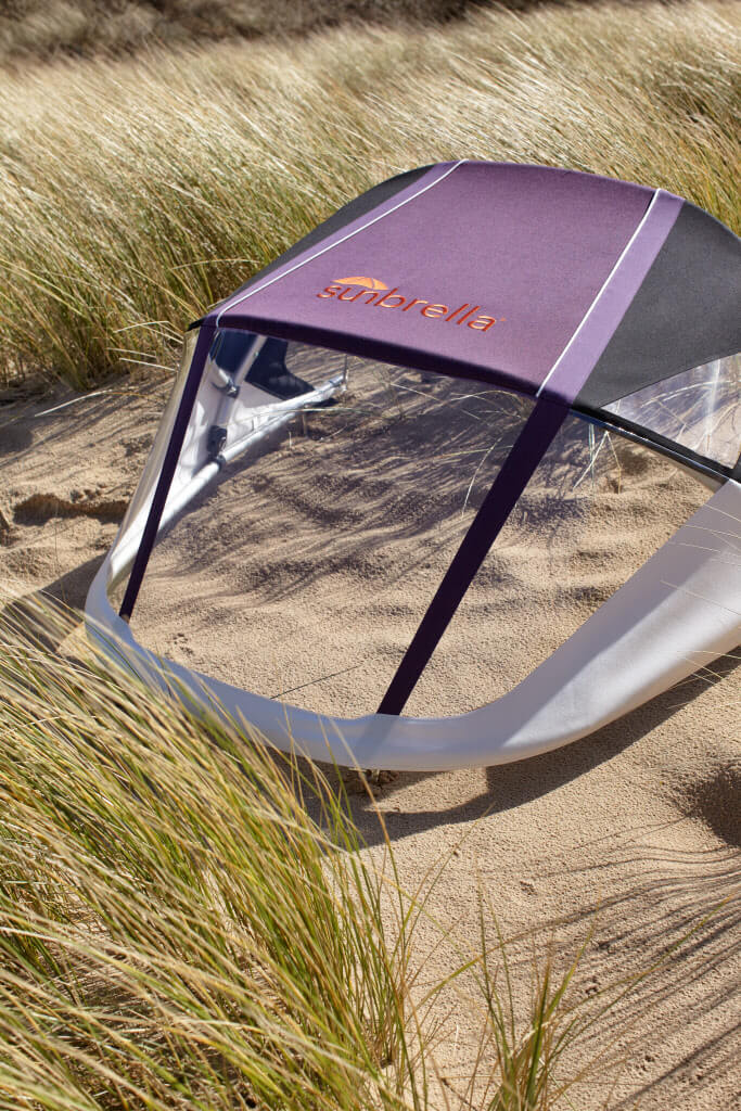 A Bimini made with purple Sunbrella fabrics sit in the sand
