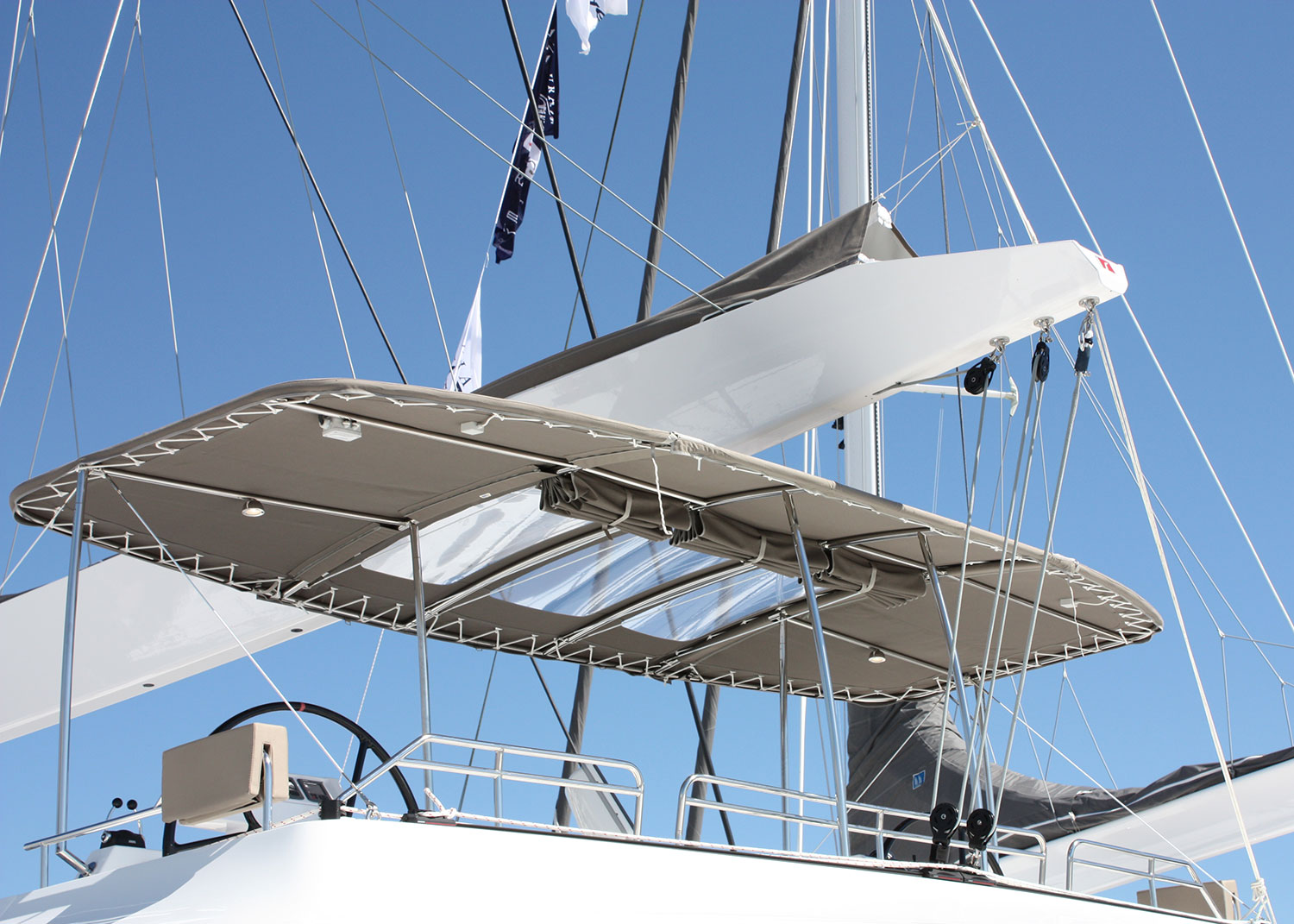 A grey bimini featuring Sunbrella fabric offers shade on a sail boat.