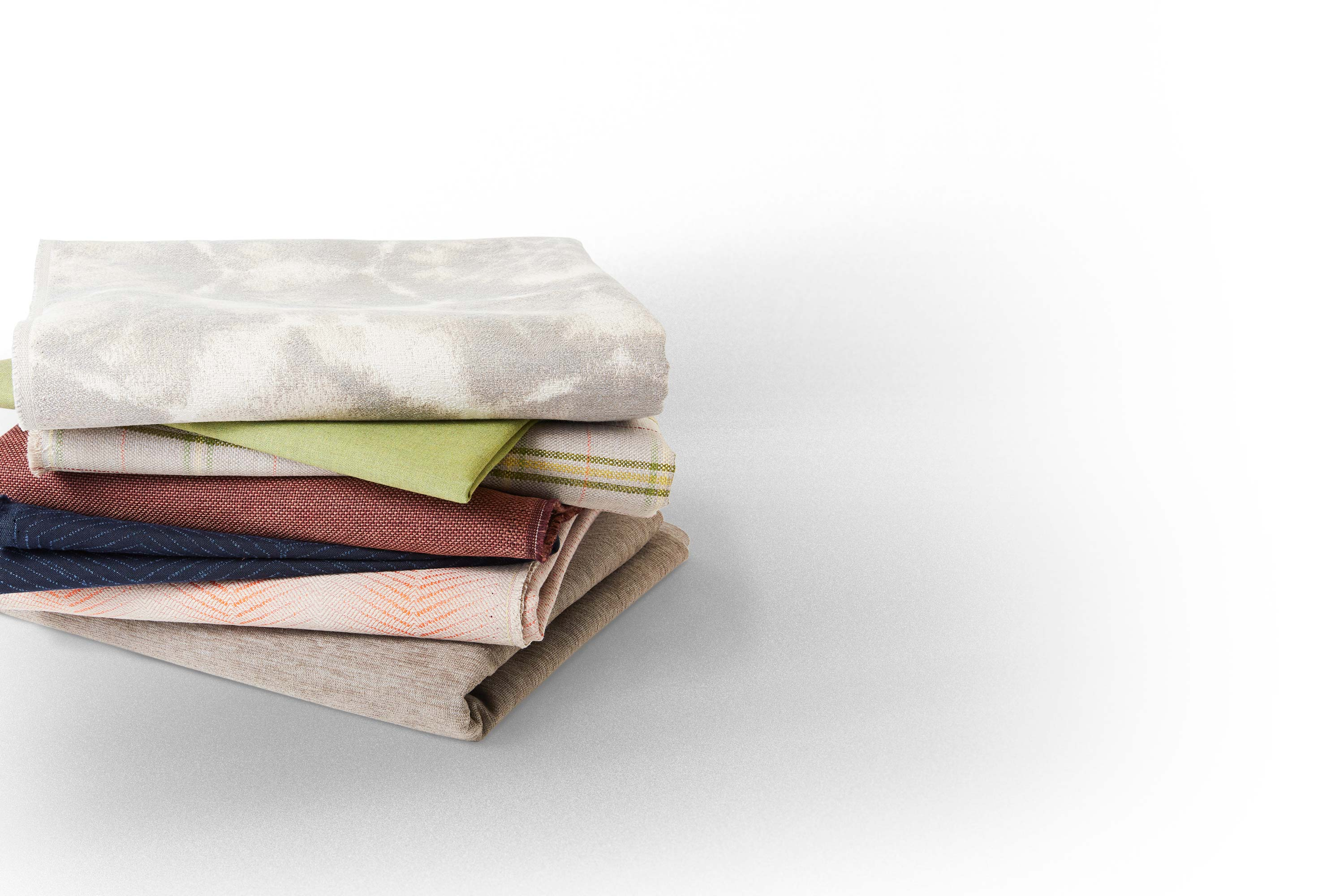 Closeup shot of a folded stack of fabric from the Sunbrella Pure Collection.